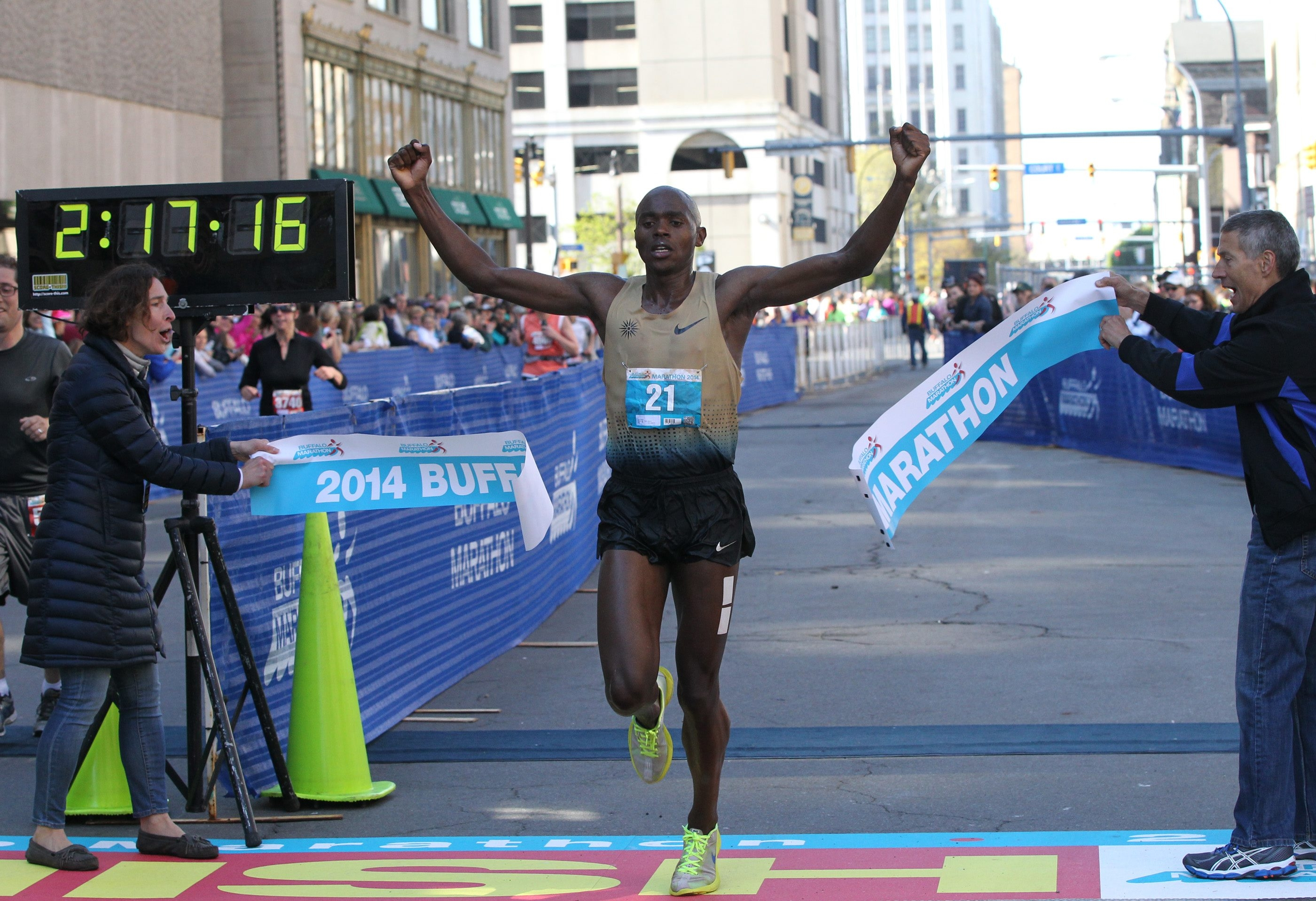 Kiplangat Tisia raises his arms in victory as he crosses the finish line in the Buffalo Marathon in record-setting fashion.  (James P. McCoy/Buffalo News)