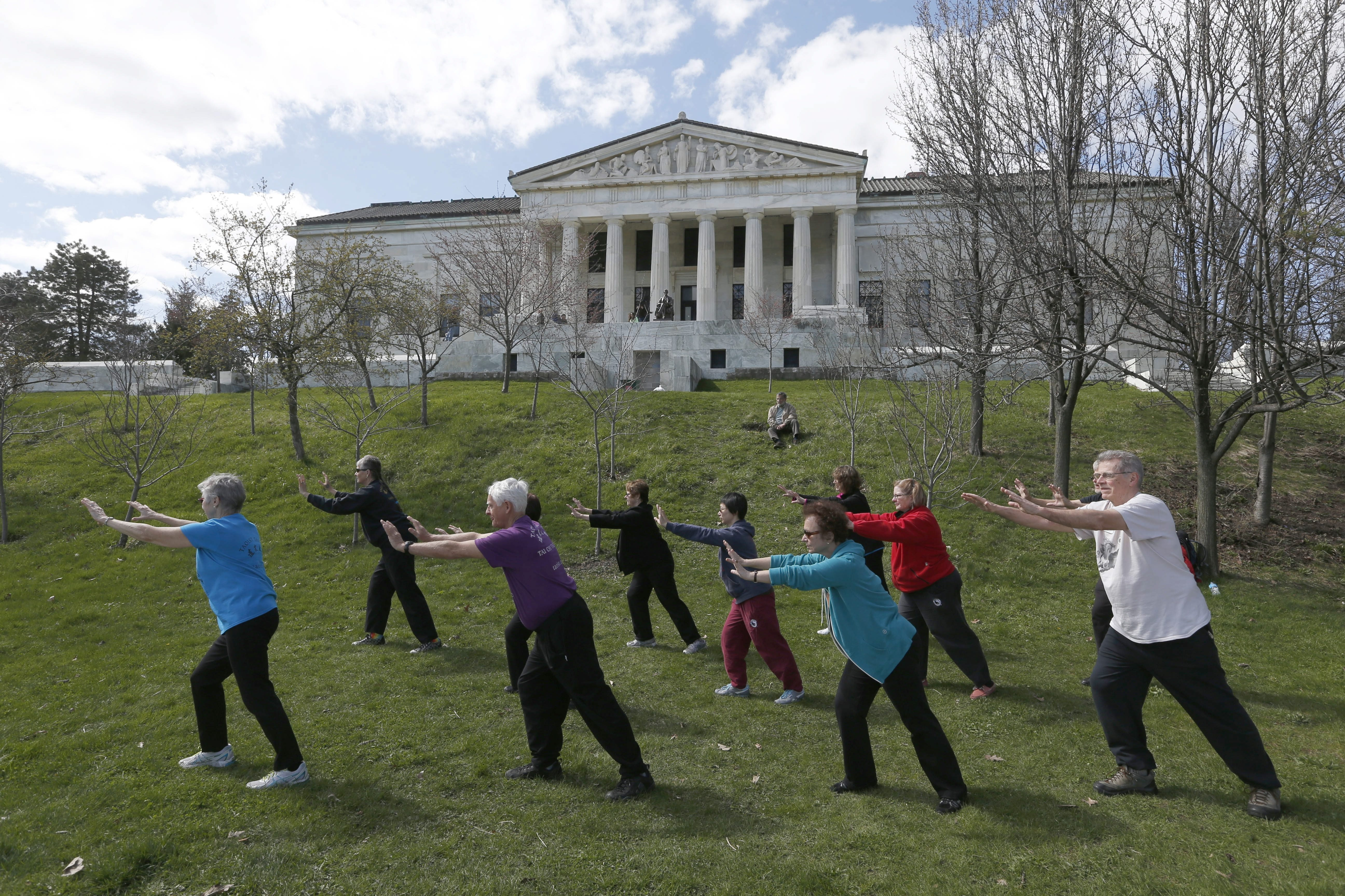A tai chi workshop uses a lawn near the lake outside the Buffalo History Museum and Japanese Garden for a serene and inspiring location.