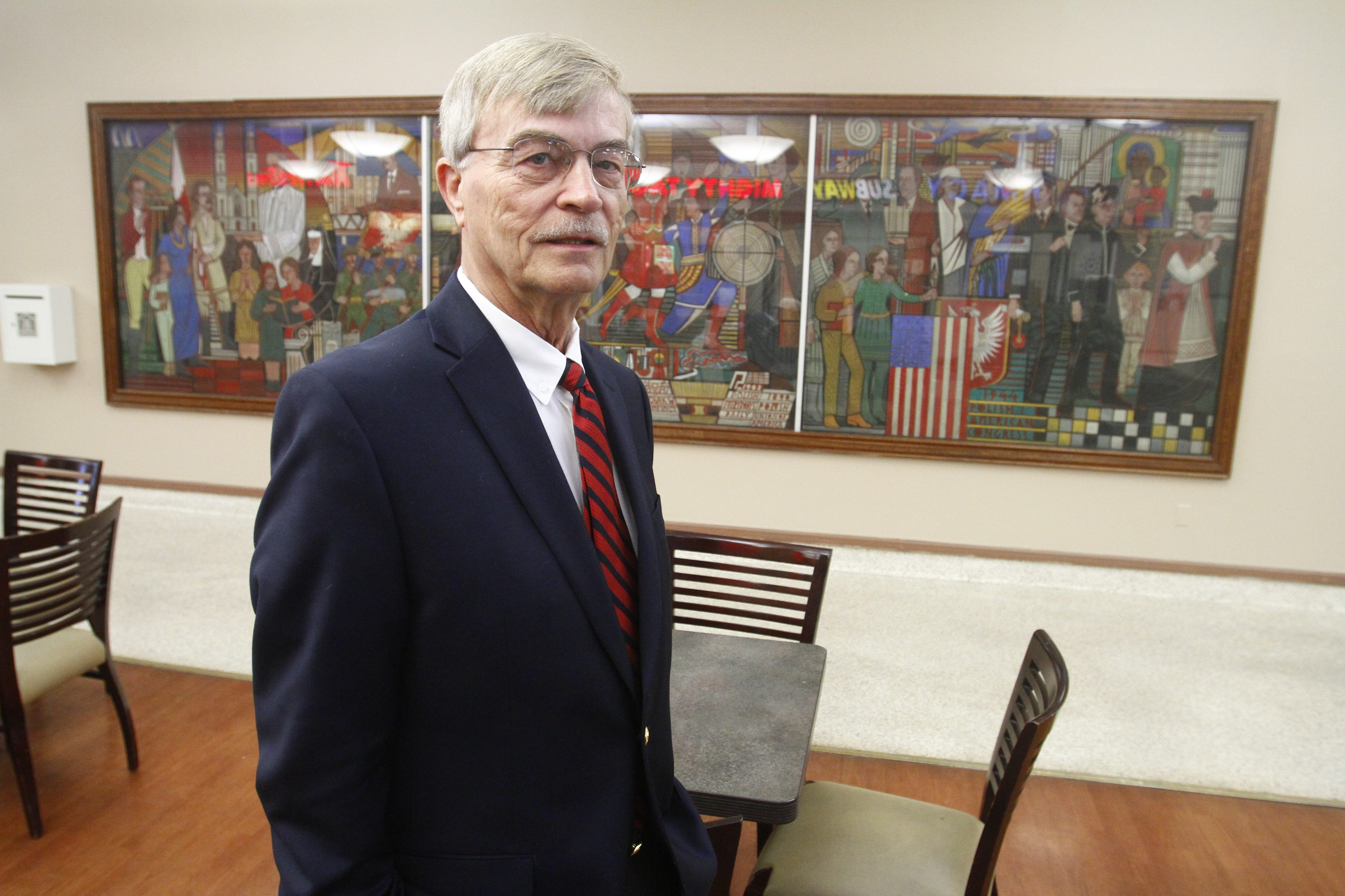 Richard Solecki, president of the Polish American Congress' Western New York Division, stands in front of a huge mural in ECMC's lobby that portrays notable people of Polish descent who have made a difference in the area.
