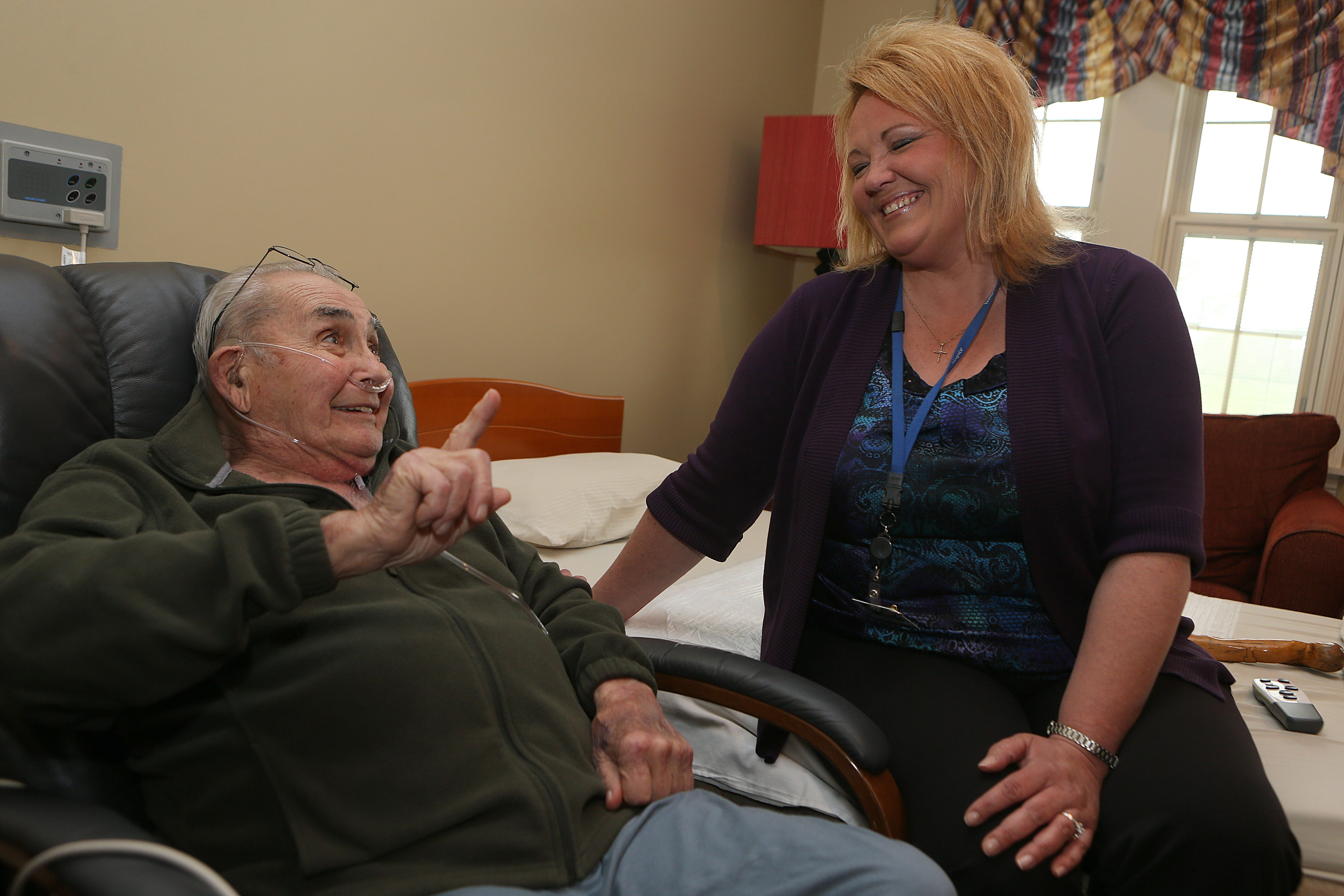 """""""I love my job here. You're making somebody comfortable being home."""" – Keri Collins, Niagara Hospice employee, here chatting with patient Edward Clayton"""