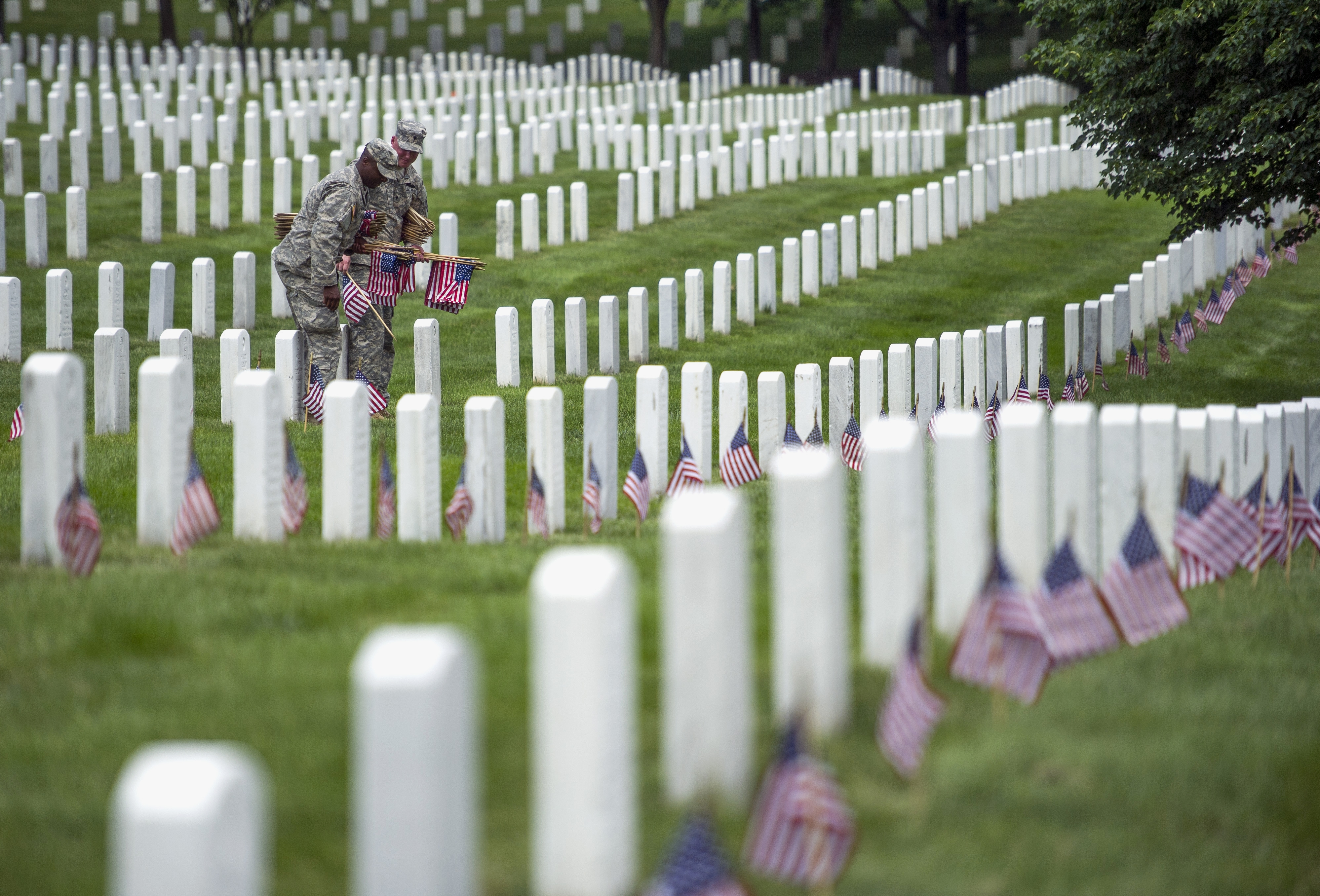 Soldiers placed flags on graves at Arlington National Cemetery Thursday in advance of Memorial Day.  Arlington has become the final resting place for more than 400,000 veterans and their family members.