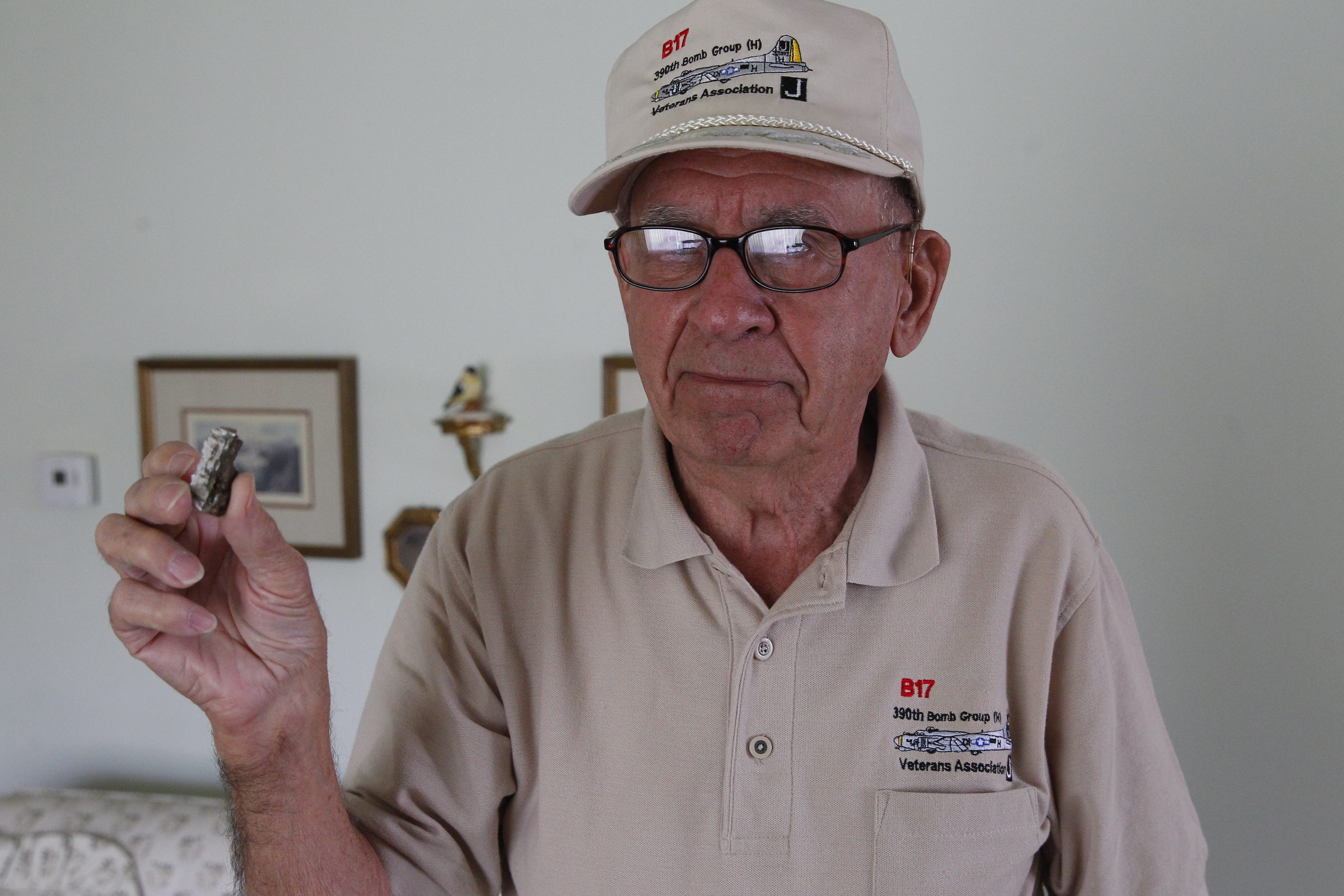 """Everett Fitchlee, a WWII Army Air Forces veteran holds a piece of  shrapnel that was removed from his back during the war. He flew some 30 missions on a Boeing B-17 """"Flying Fortress."""""""