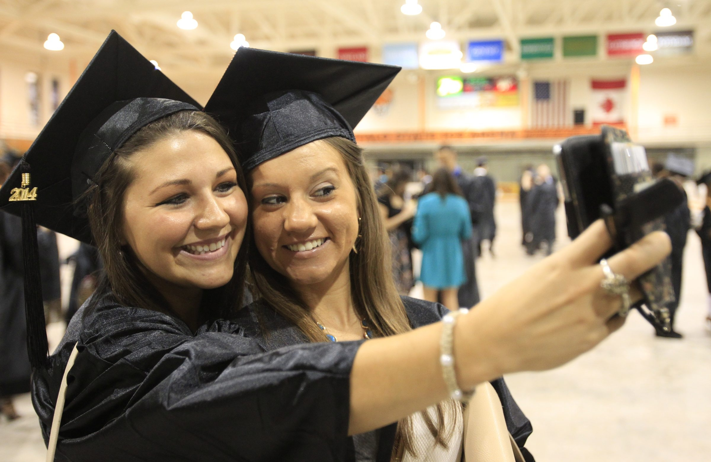 Erie Community College students Jessica Cramer, left, and Jenna Arcuri take a selfie prior to graduation at the Buffalo State Sports Arena on Wednesday. See a photo gallery at BuffaloNews.com.