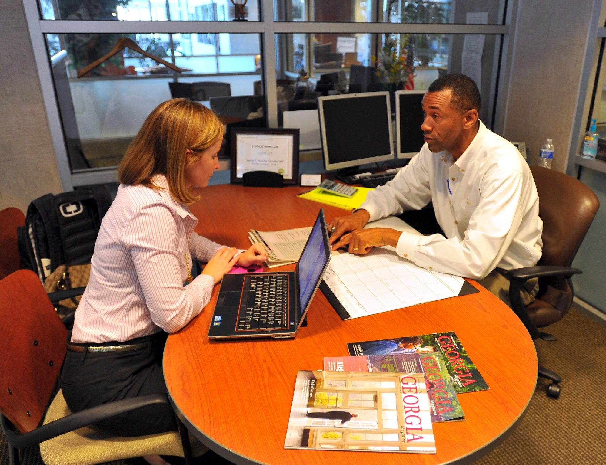 Lexus salesman Horace McMillan, right, reviews warranty information with car buyer Jennifer Williams at a dealership in Smyrna, Ga.