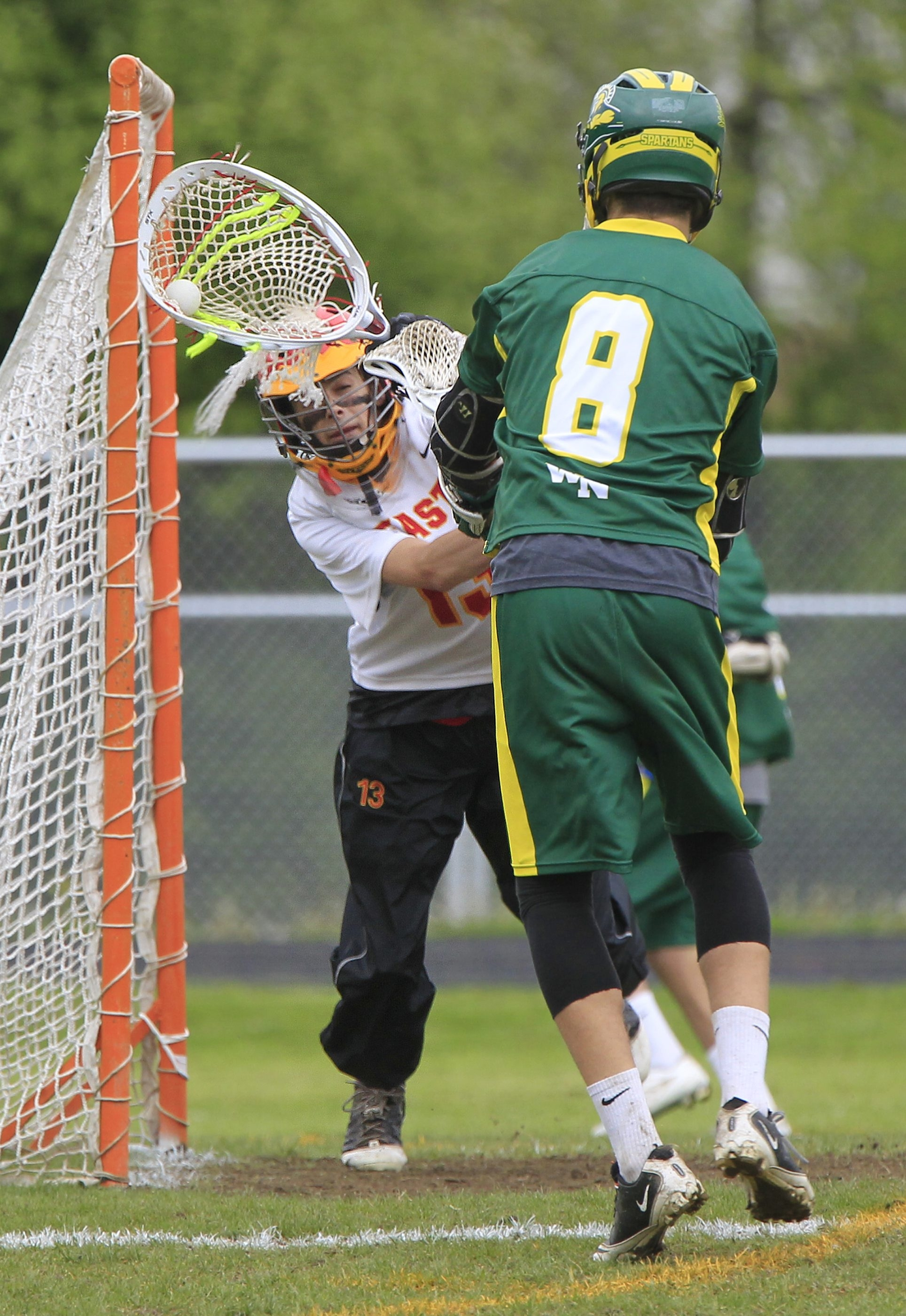 Williamsville East goaltender Connor Lalime (13) makes a save on Williamsville North player Chad Steinwachs in a win by East, 11-9.