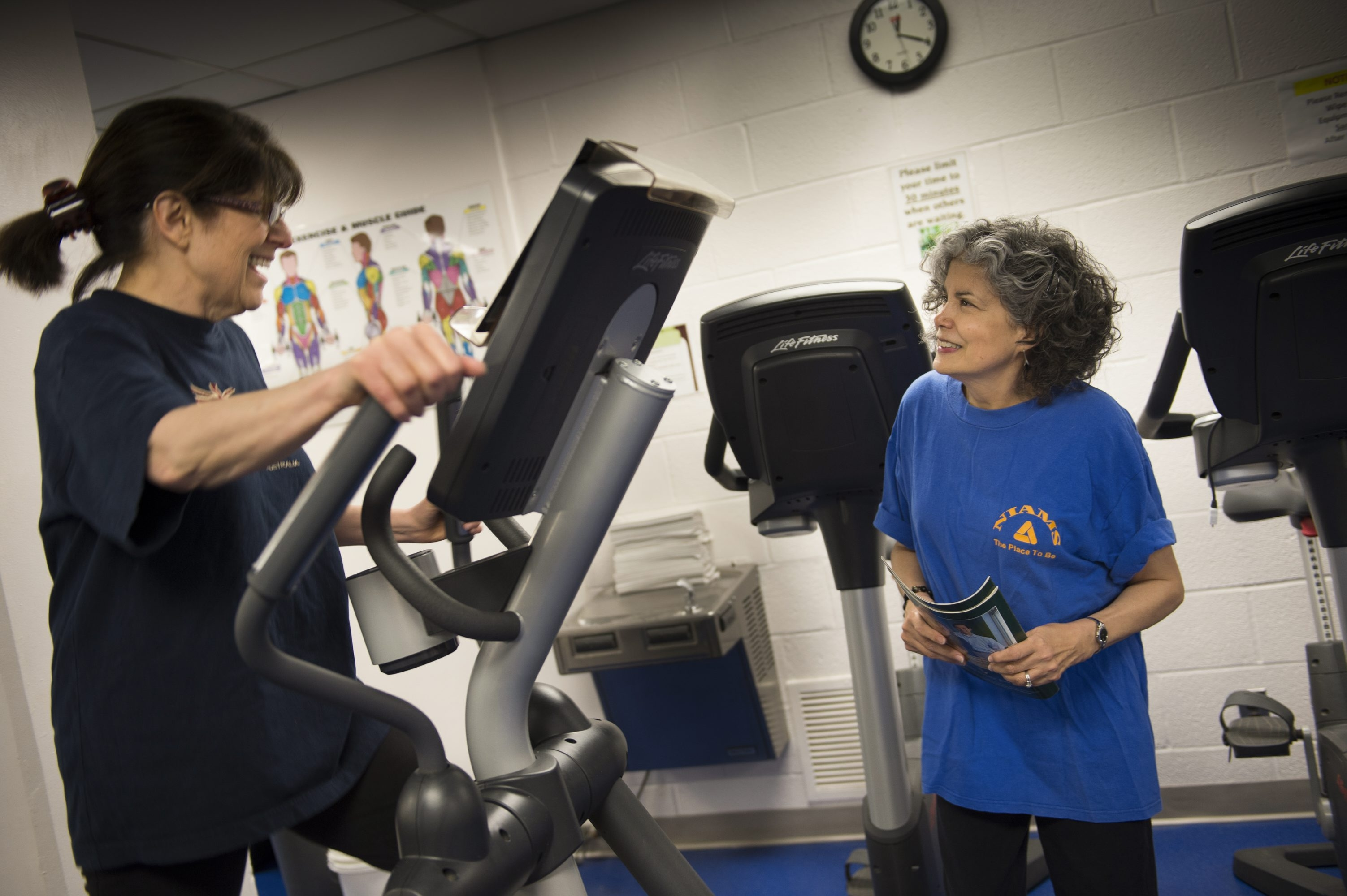 Ann Bodmer, left, and Robyn Strachan work out in a gym at the National Institutes of Health offices in Bethesda, Md. Many employers are offering programs designed to retain older workers.