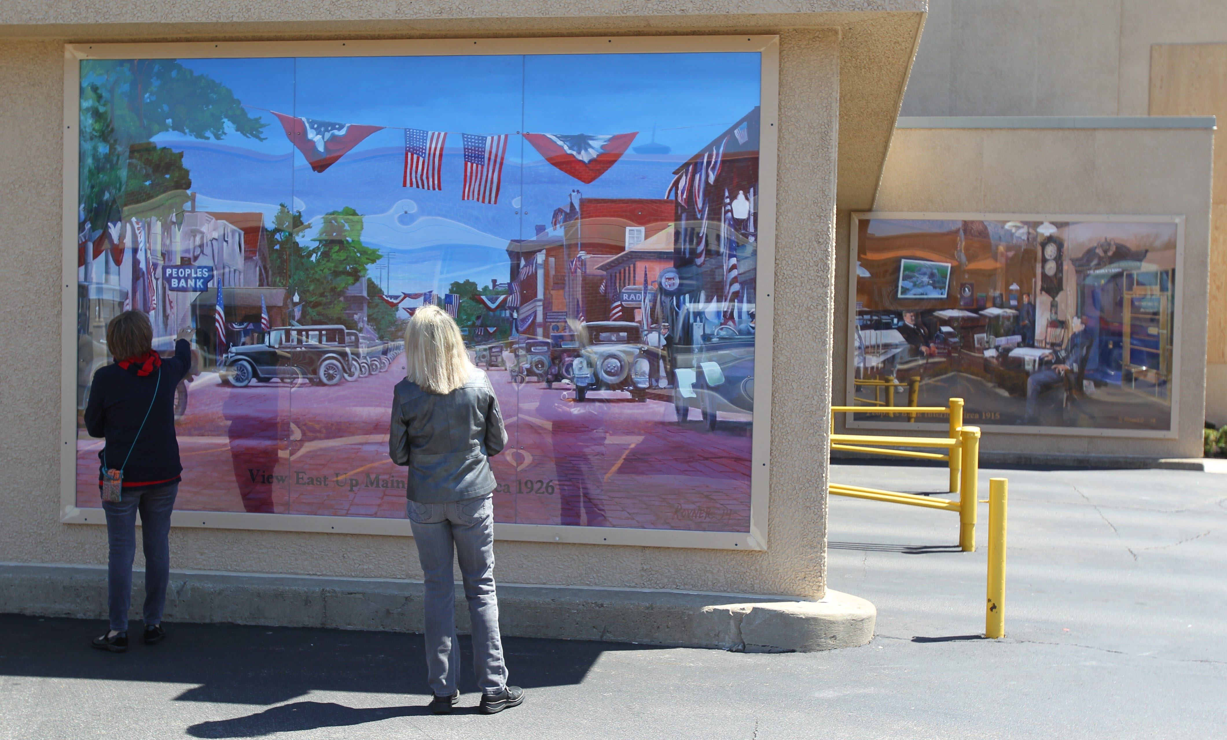 Annette Flynt, left, and Pam Patterson check out one of the new murals on the wall of the Bank of America building on Main Street in the Village of Hamburg.