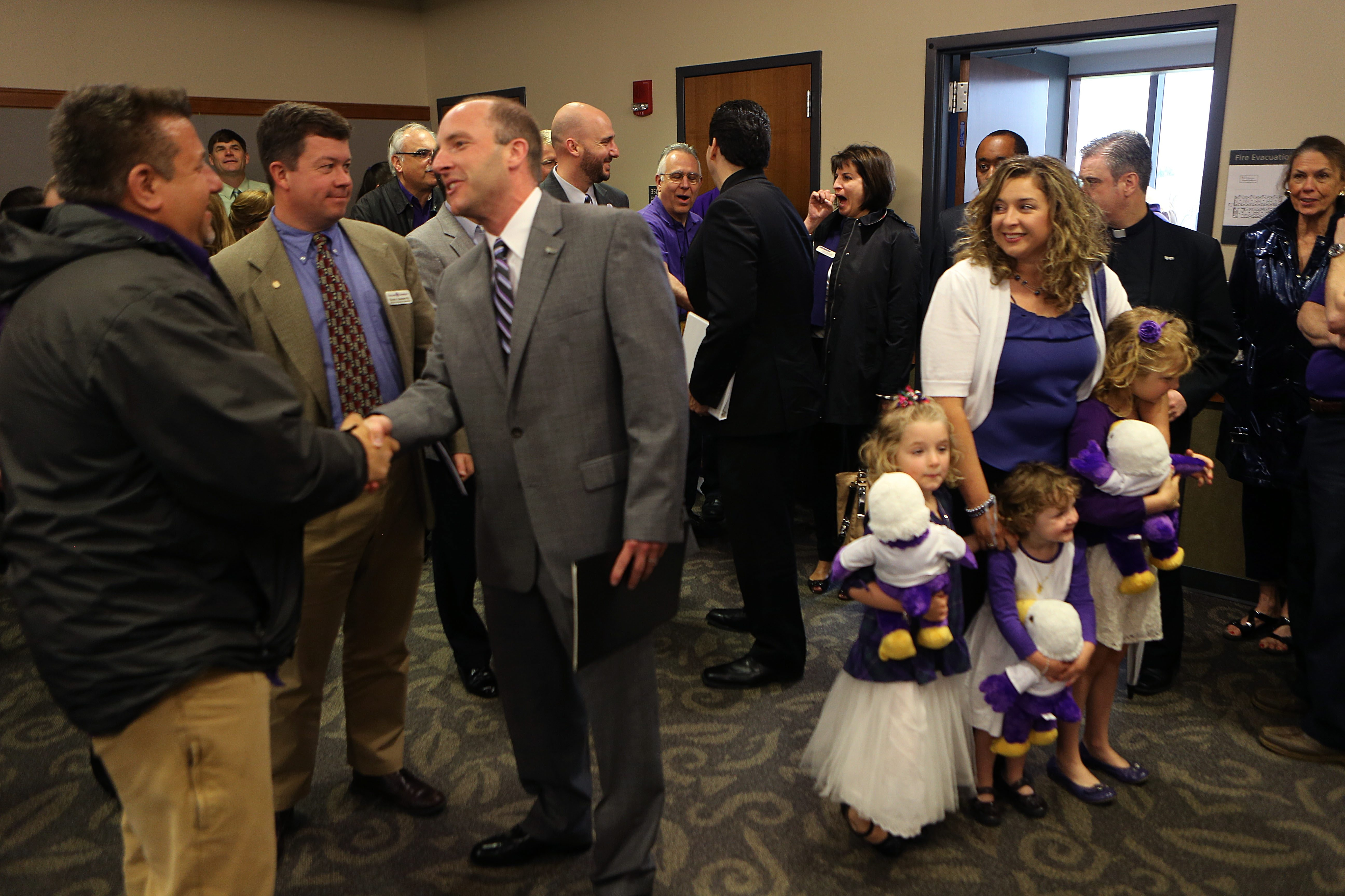 New athletics director Simon Gray, third from left, greets attendees at a gathering in Bisgrove Hall on the Niagara University campus in Lewiston, as his wife, Anne Christine, manages three daughters, Emilie, 7, Elisabeth, 5, and Caroline, 2, all dressed in school purple.