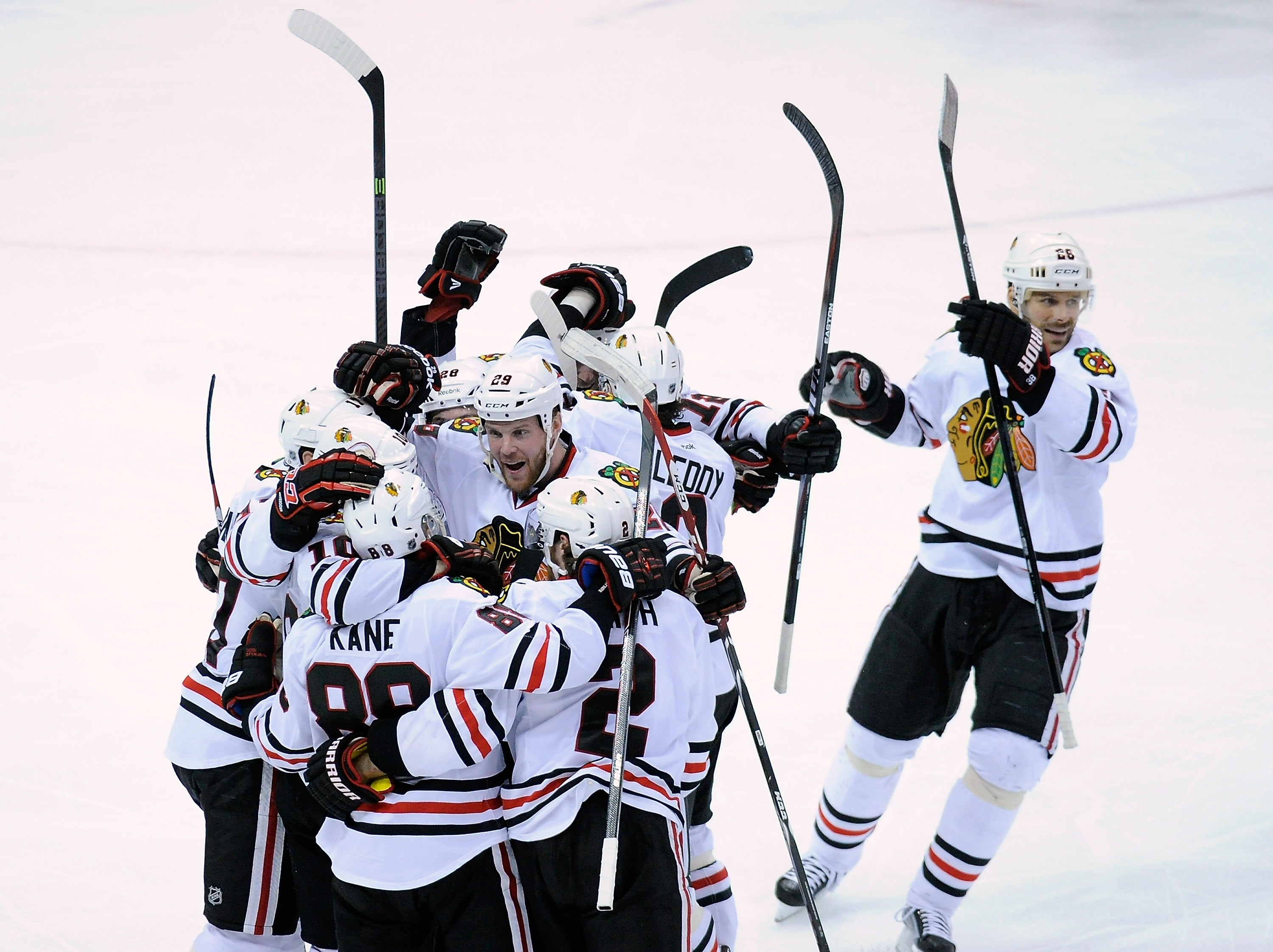 Patrick Kane is embraced by his teammates after scoring the winning goal in overtime to eliminate Minnesota in Game Six Tuesday.
