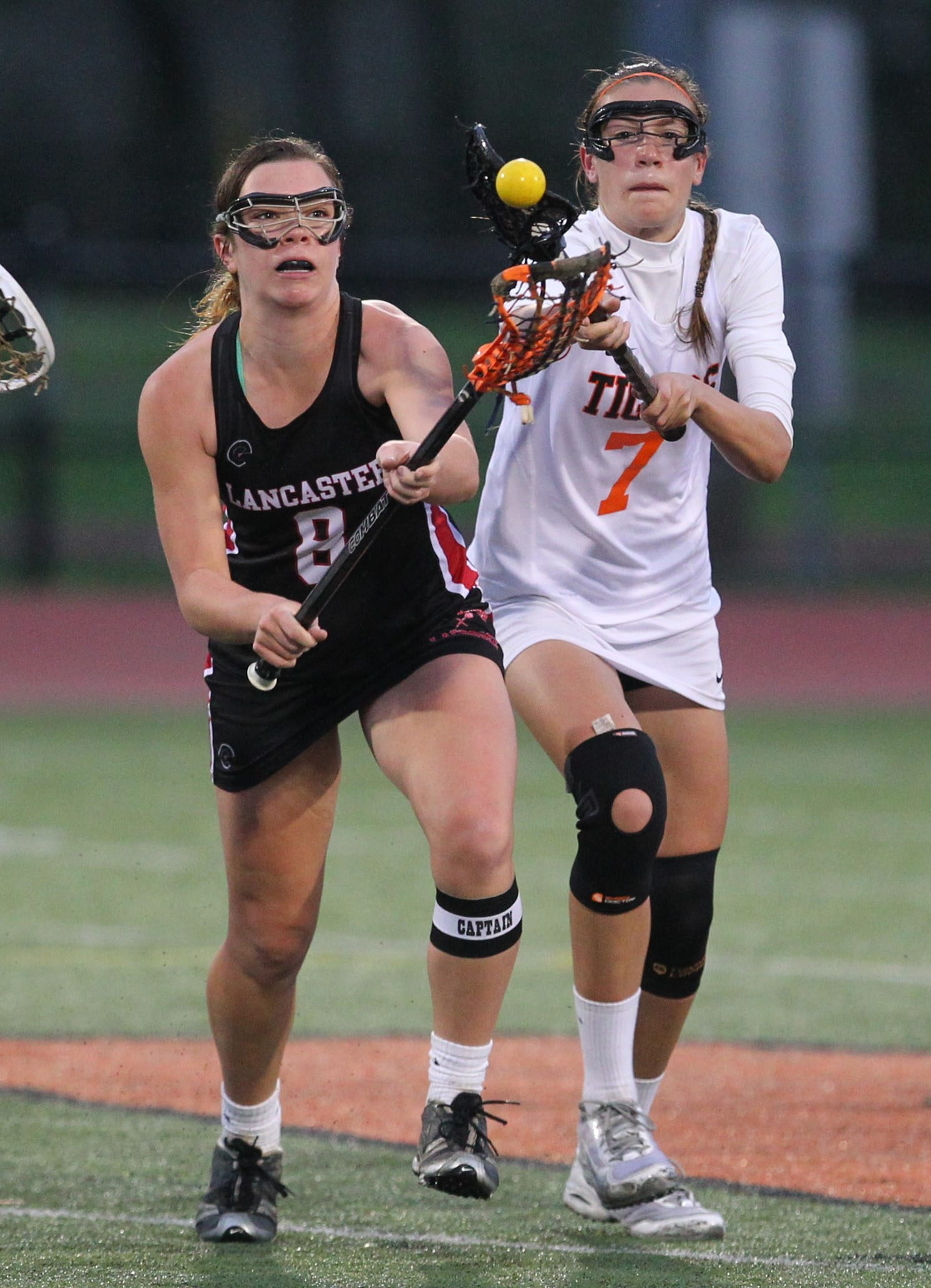 Grace Gabriel beats Amherst's McKenna Rushford to a loose ball during Lancaster's 9-7 win Thursday.