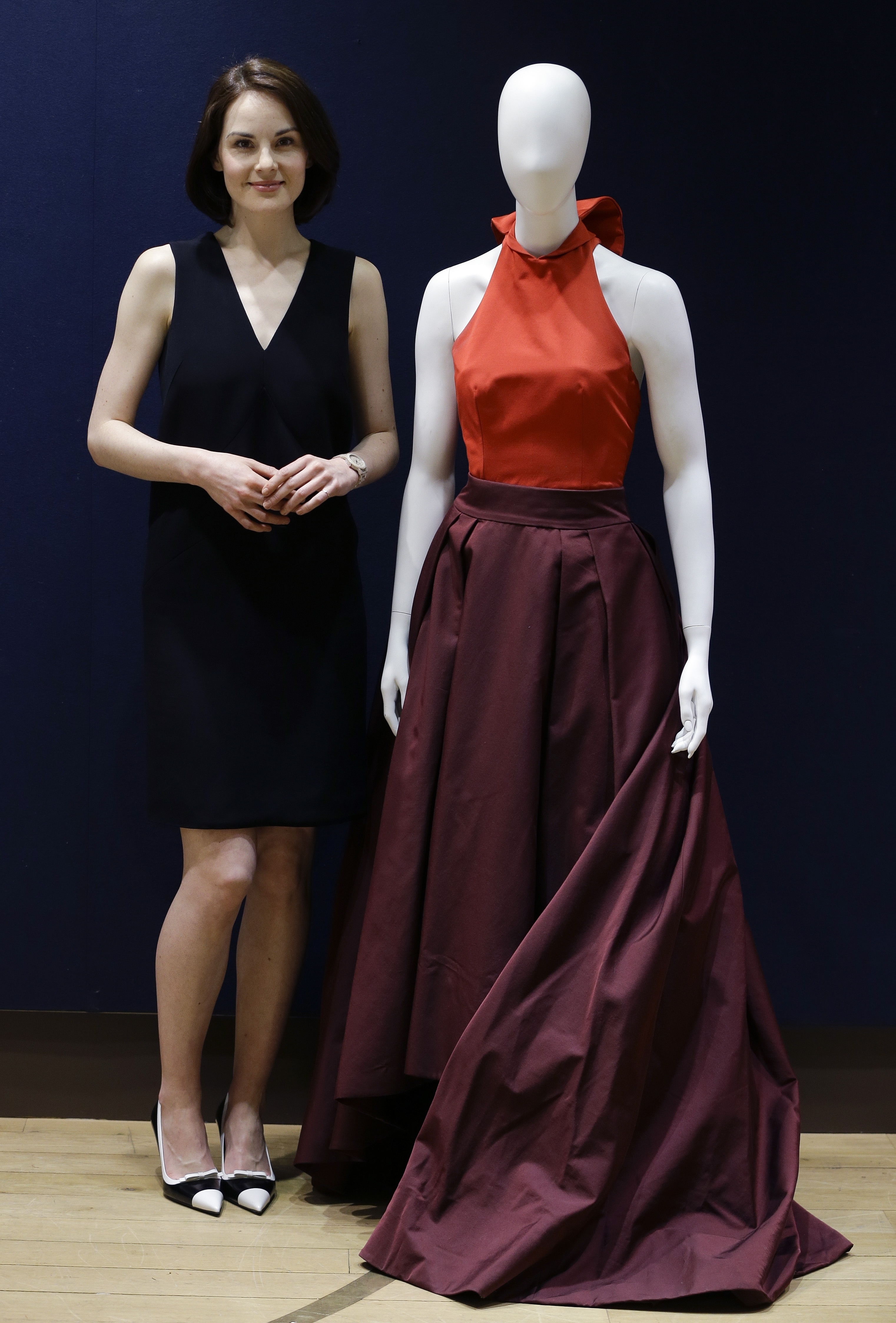 Michelle Dockery stands with the Prada gown she wore to the 2013 Emmy's, at Christie's auction rooms in London.