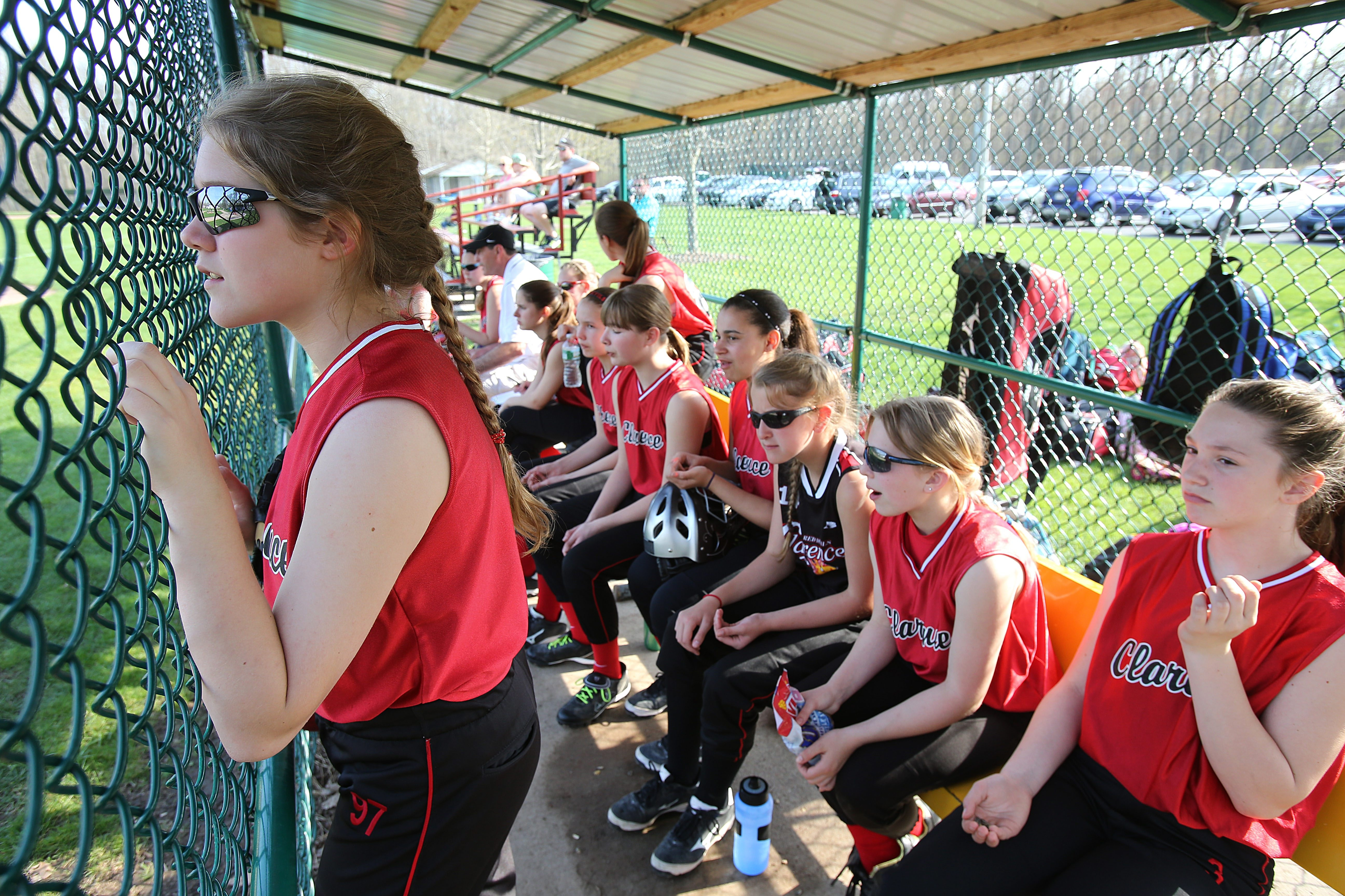 Natalie Sirface, left, of the Clarence modified softball team watches the action with her teammates from the dugout at Jeffrey P. Brownschidle Field in Clarence Town Park.