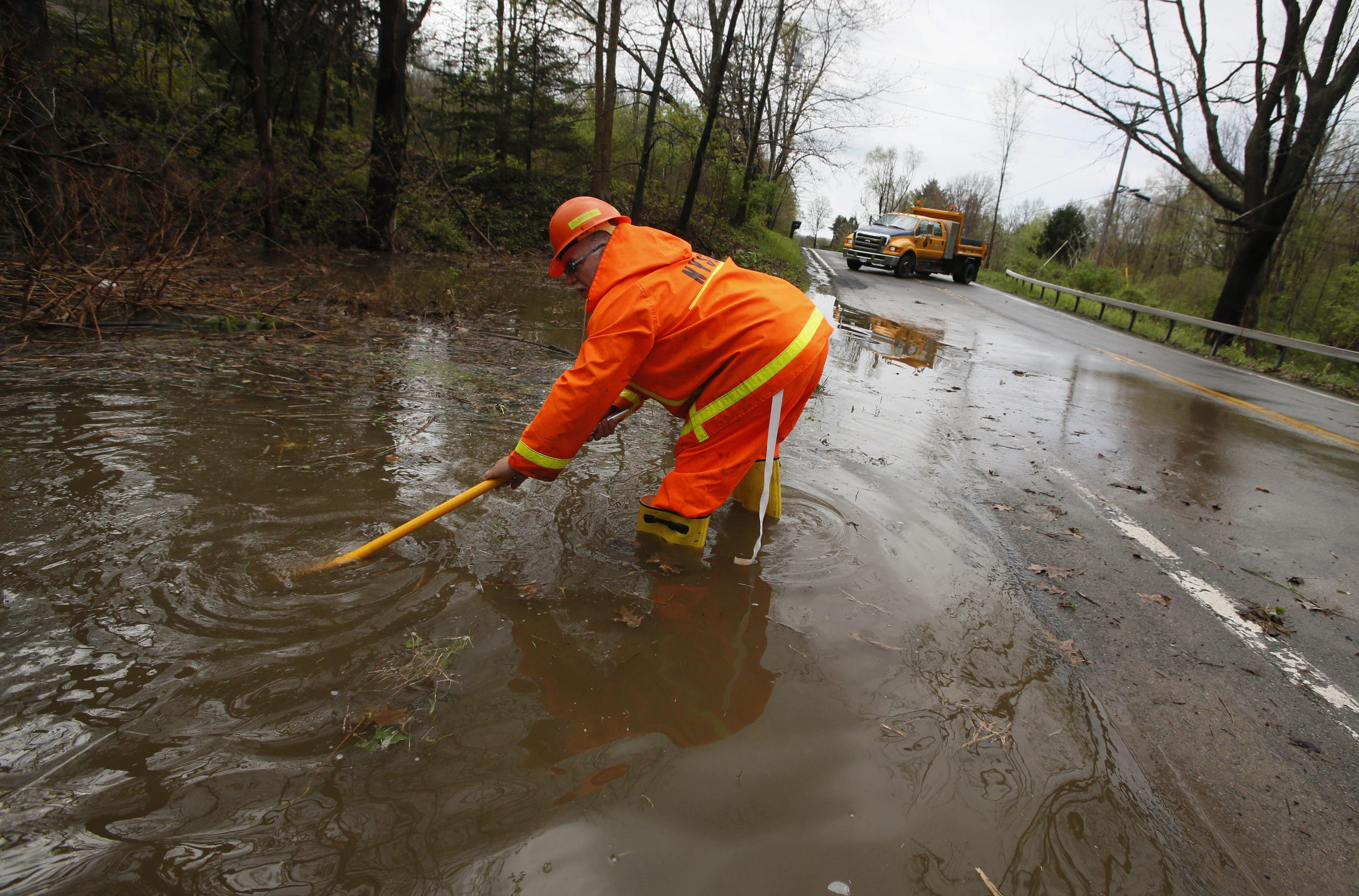 State DOT worker Terry Lillie attempts to clear a drain that flows beneath Versailles Plank Road on the Seneca Nation of Indians' Cattaraugus Reservation today.