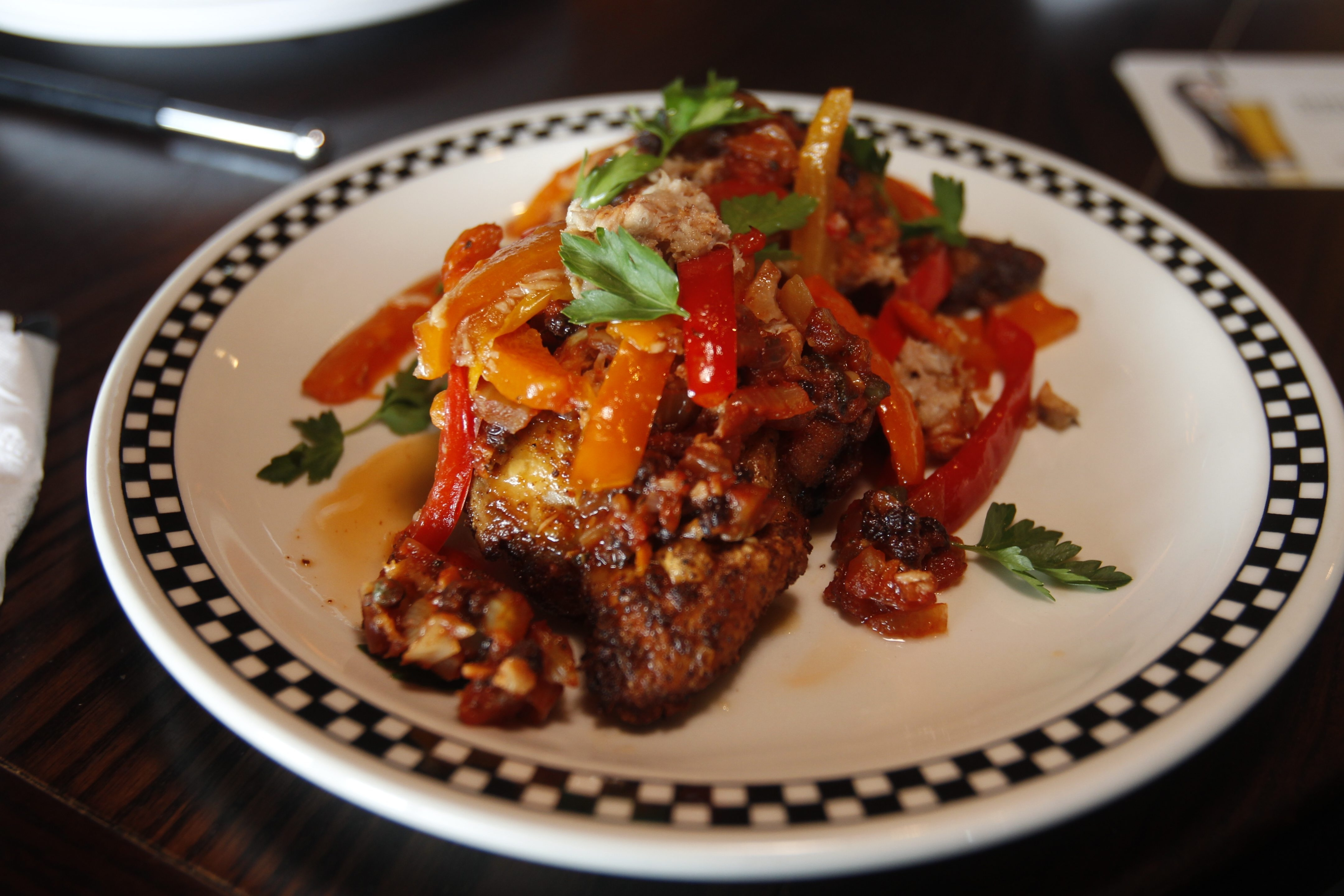 Rocco's crisps up skin-on chicken thighs in the wood oven and serves them with a sweet-and-sour Sicilian relish and a scattering of vinegar peppers at  Rocco's in Clarence, N.Y. (John Hickey / Buffalo News)