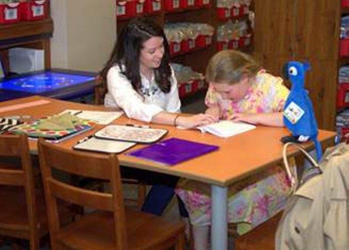 Niagara University student Kristen DeMarco helps Sally Rick in the university's Family Literacy Center.