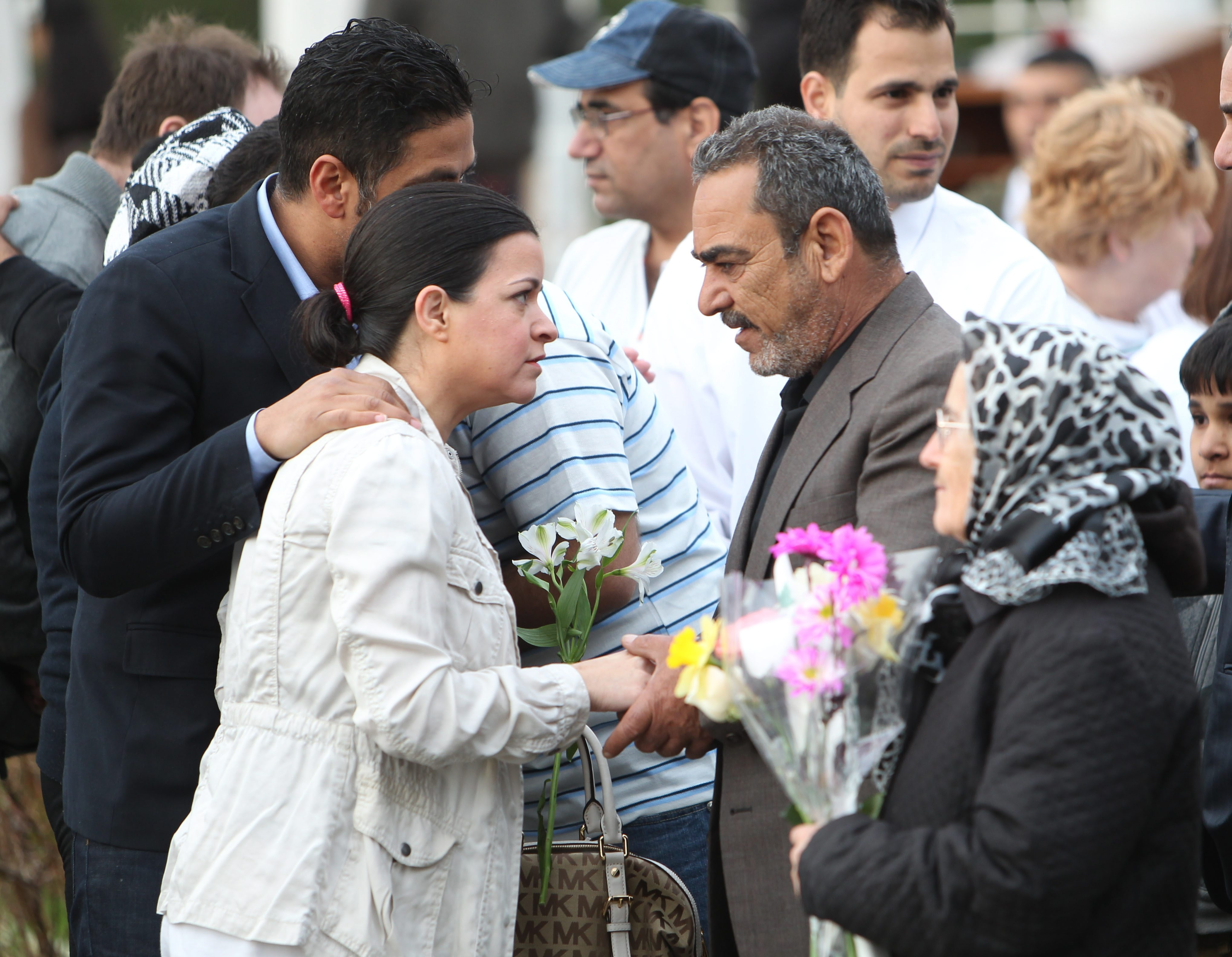 The Iraqi American Society organized a memorial service for Ameer Al Shammari at the Rose Garden at Delaware Park on Saturday. A couple offers their condolences to Ameer's father.
