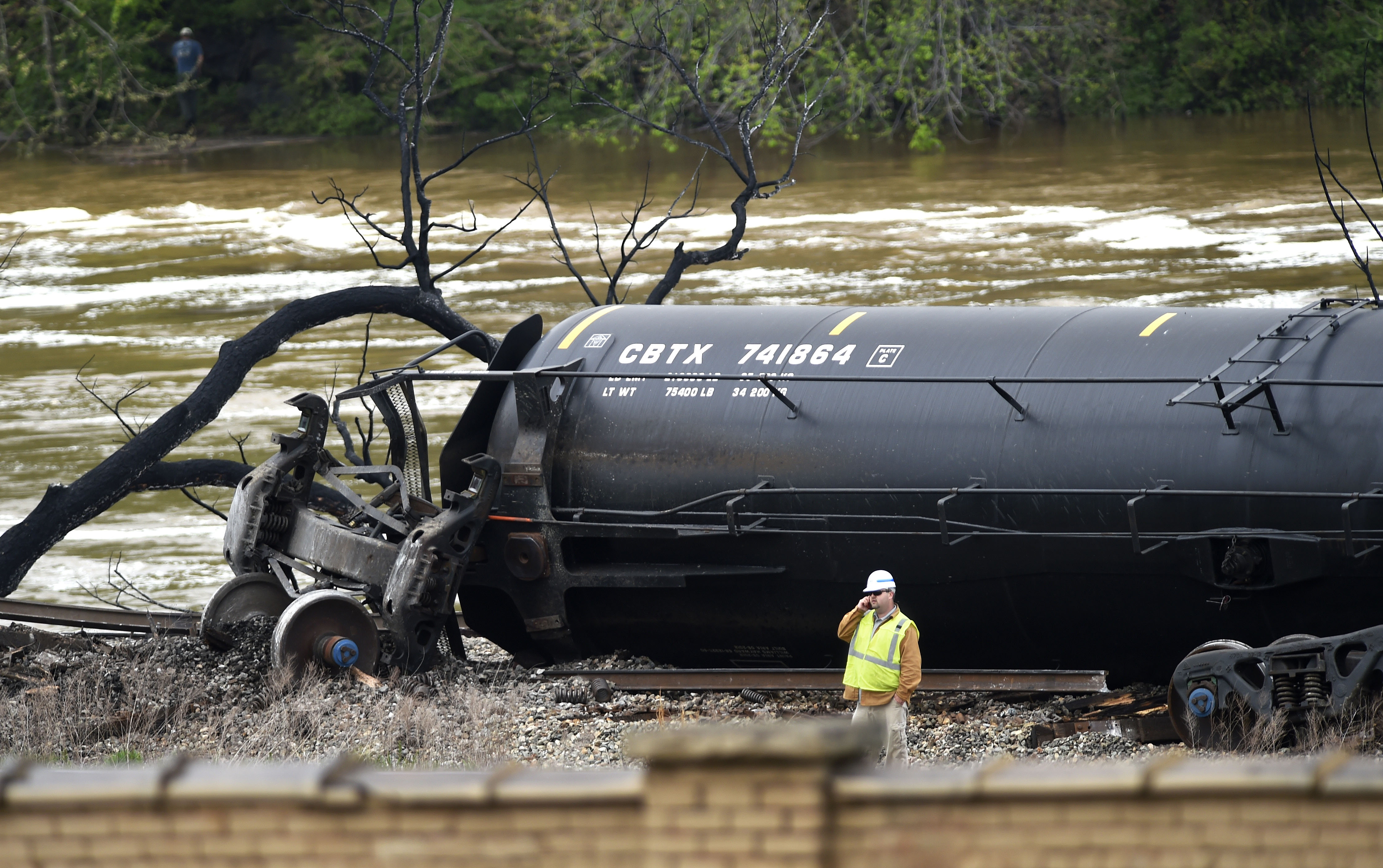 Transportation Secretary Anthony Foxx on Wednesday ordered rail companies to warn state officials when their trains are hauling crude oil or other hazardous materials through local communities. That order was spurred, in part, by the derailment of this train carrying oil in Lynchburg, Va., last week. In the photo, a worker stands by a damaged tanker car Thursday.