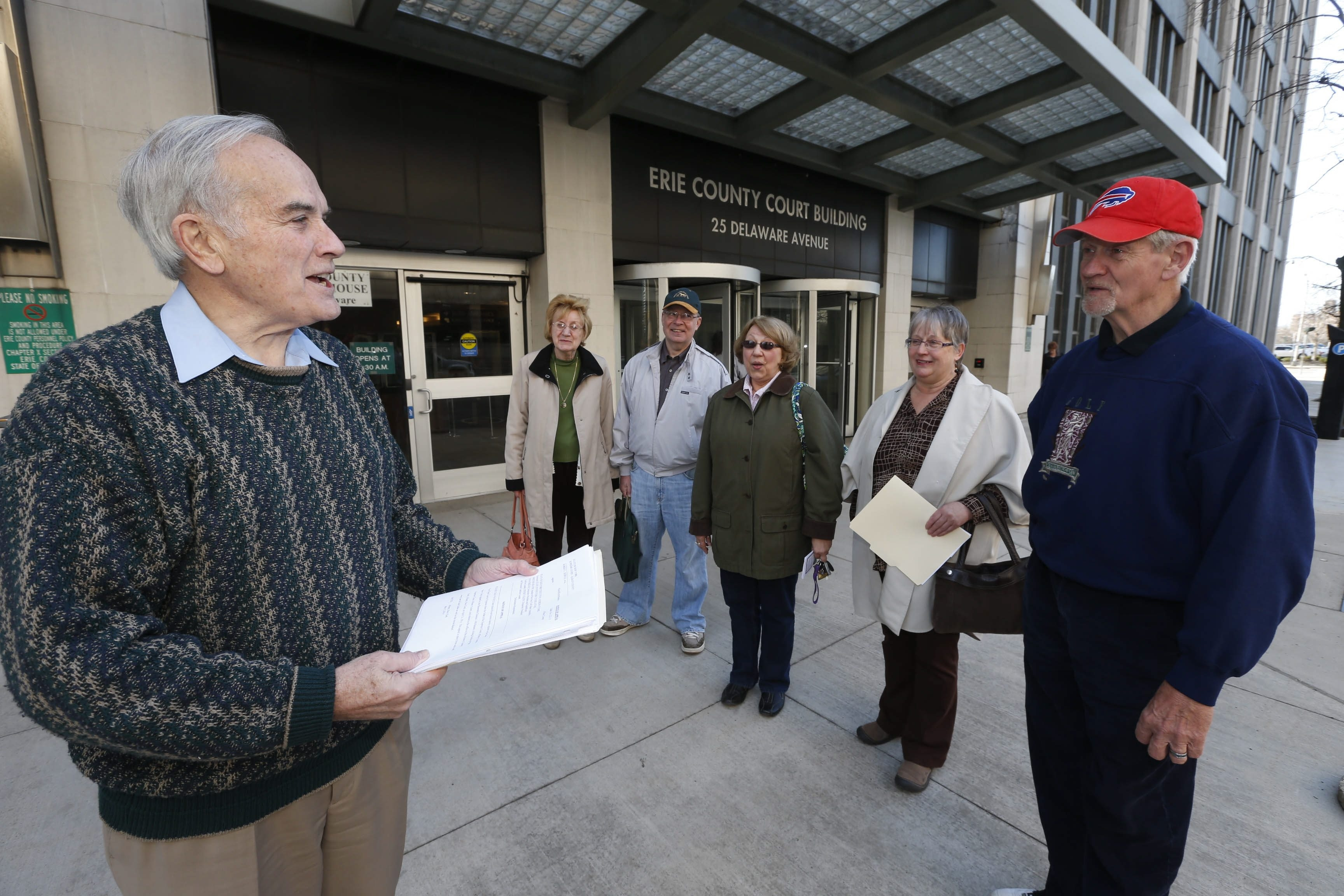 Robert Schulz, left, lead plaintiff in a lawsuit challenging the SAFE Act, speaks Monday with fellow plaintiffs outside the Erie County Courthouse on Delaware Avenue.