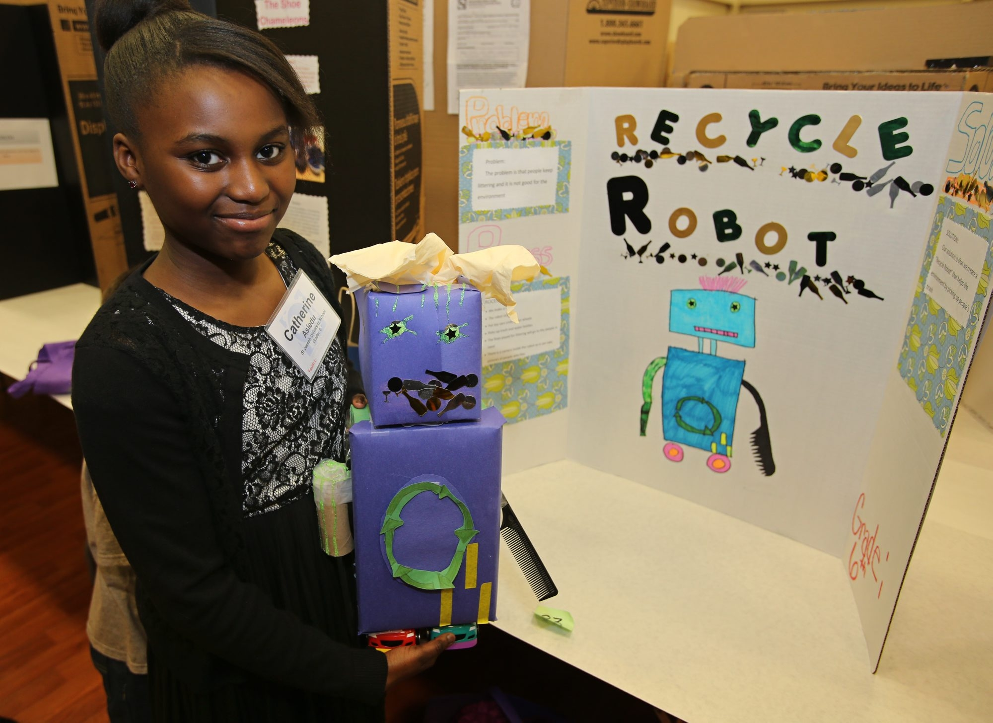 """Catherine Asiedu, 11, of Amherst, proudly displays her invention, """"Recycle Robot,"""" on Sunday during the Invention Convention at the Sullivan Campus Center at Medaille College."""