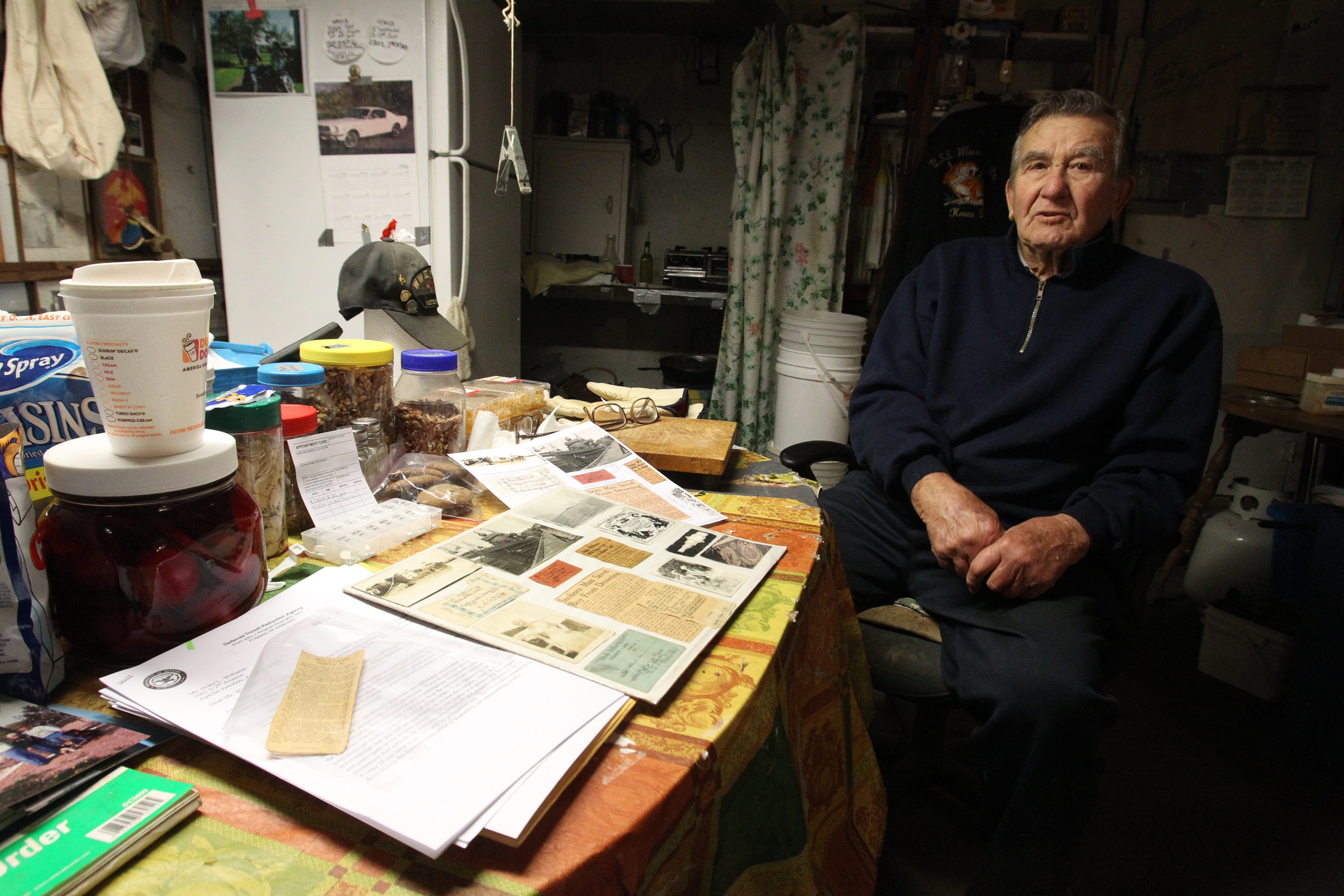Duke L. Williams revisits a scrapbook, evoking wartime memories, at his Lewiston home near the Manhattan Project storage facility.