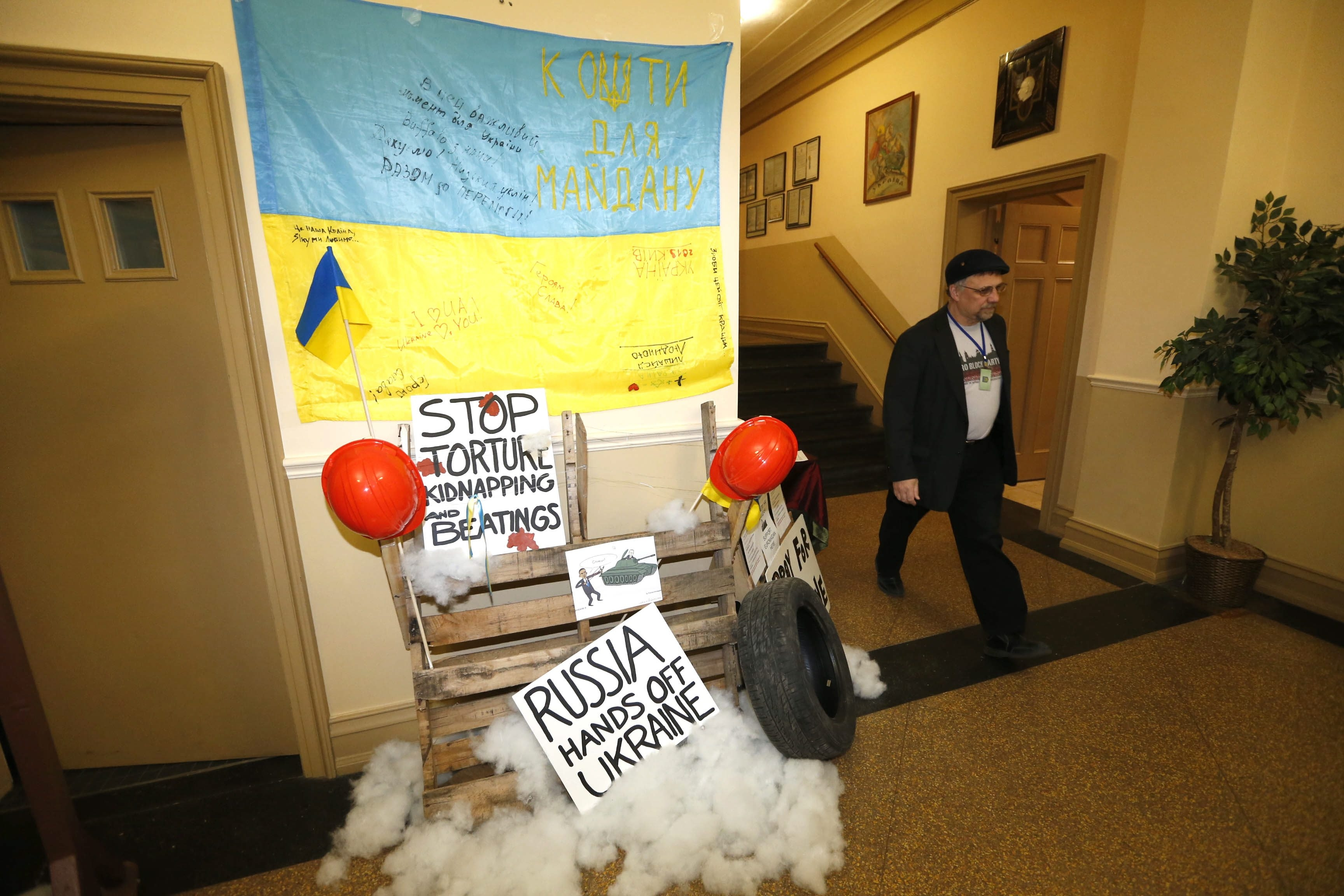 Emil Bandriwsky walks by a signed Ukrainian flag that was present at the recent uprising against Russia in that country. It is displayed above a tribute memorial in the Dnipro Ukrainian Culture Center's lobby on Genesee Street.
