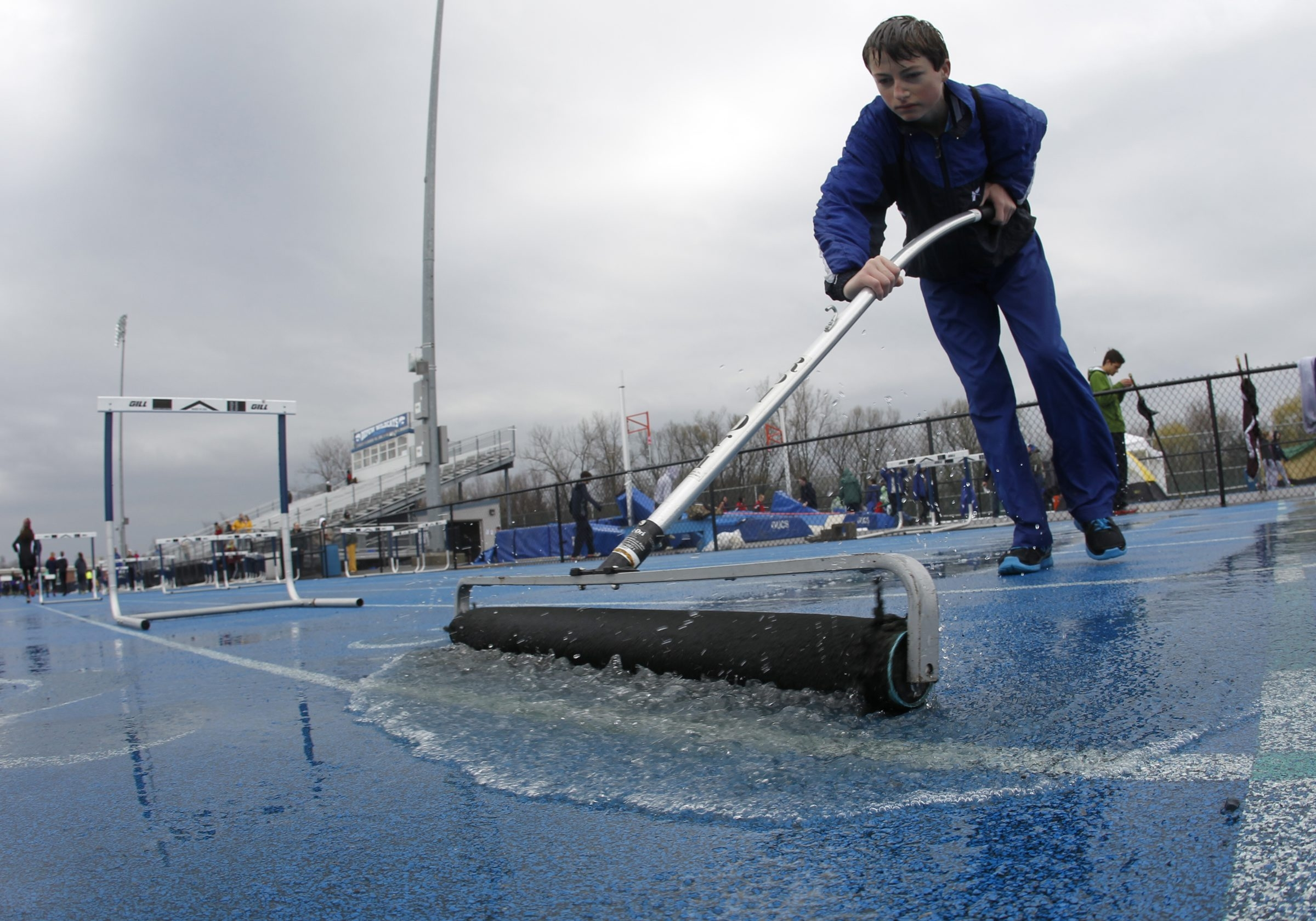 Kyle Kavanagh,16, works on squeegeeing the water from the track prior to the Depew Wildcat relays at Depew on April 26. Harry Scull Jr. /Buffalo News