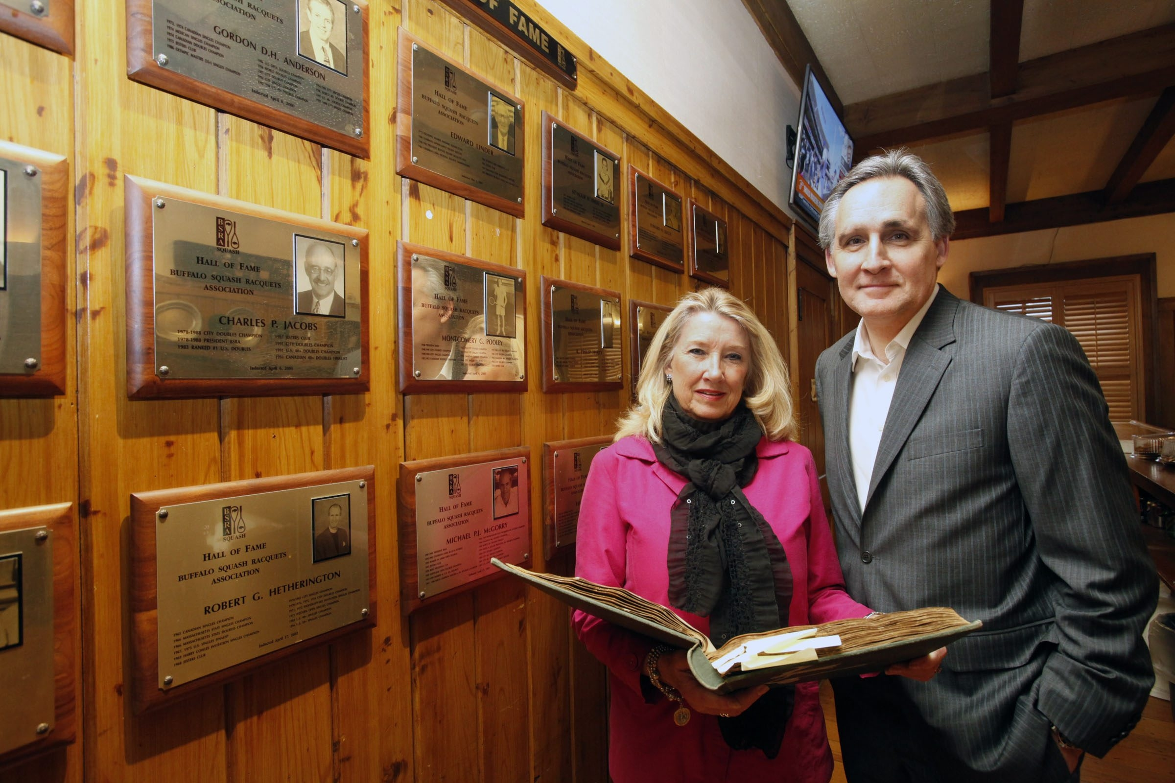 Sally Russell and Richard Lynn look over a scrapbook commemorating the 80th year of the Buffalo Squash Association.