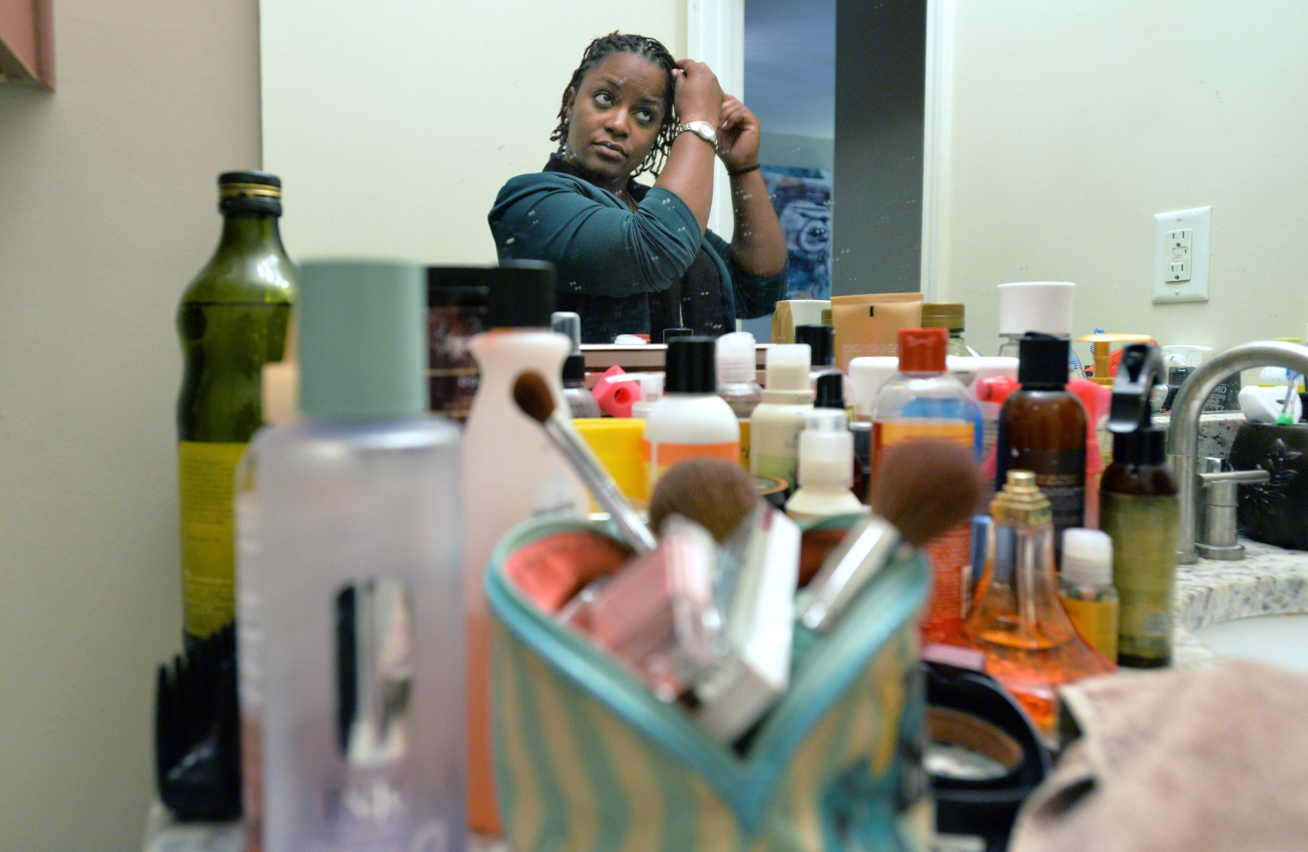 Former National Guard soldier Jasmine Jacobs uses many hair products daily at her home in Atlanta. She left the National Guard after the Army banned hair twists.