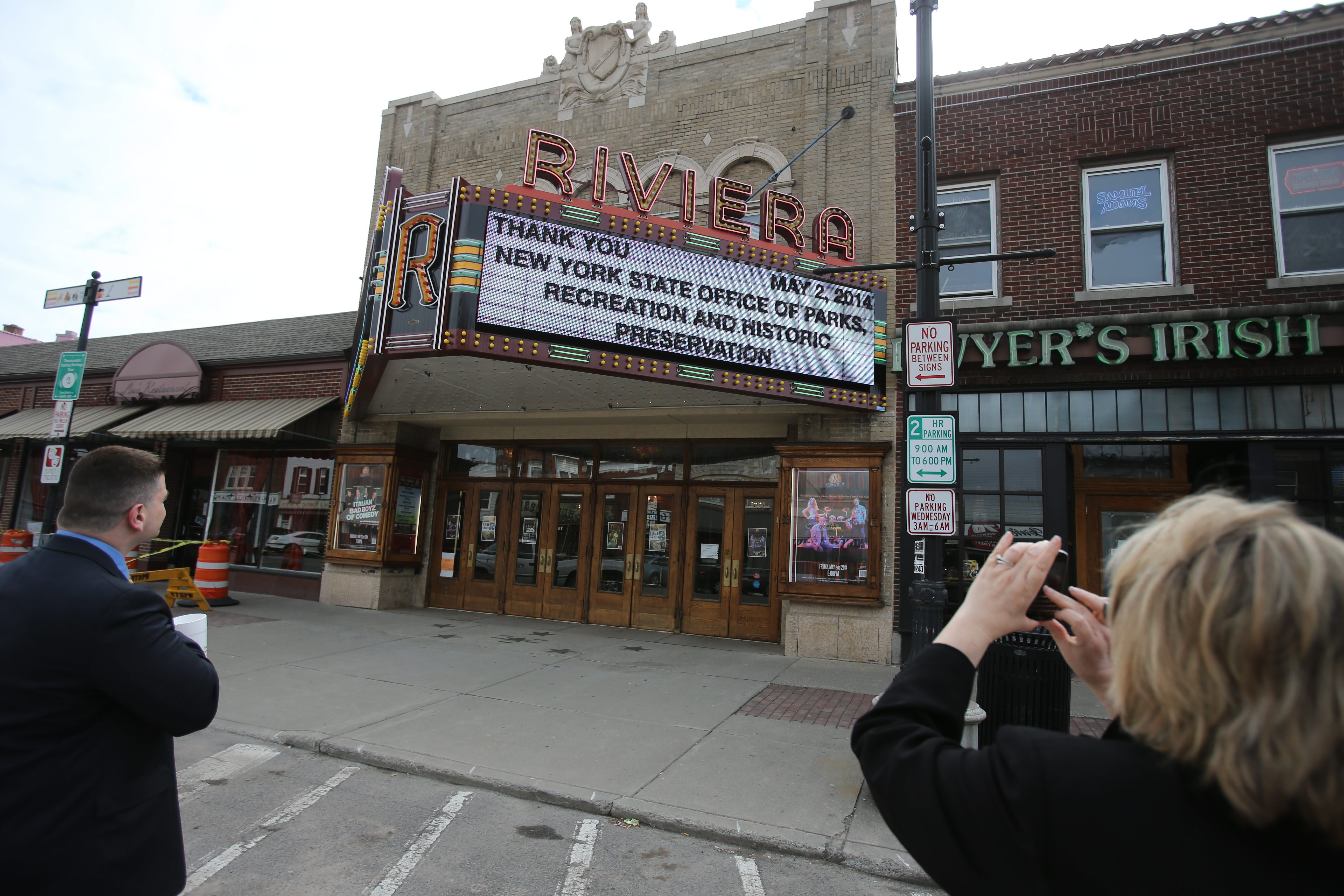 Gary J. Roleau, director of development, and Pamm Lent of Empire State Development admire the restored marquee at the Riviera Theatre in North Tonawanda Friday.