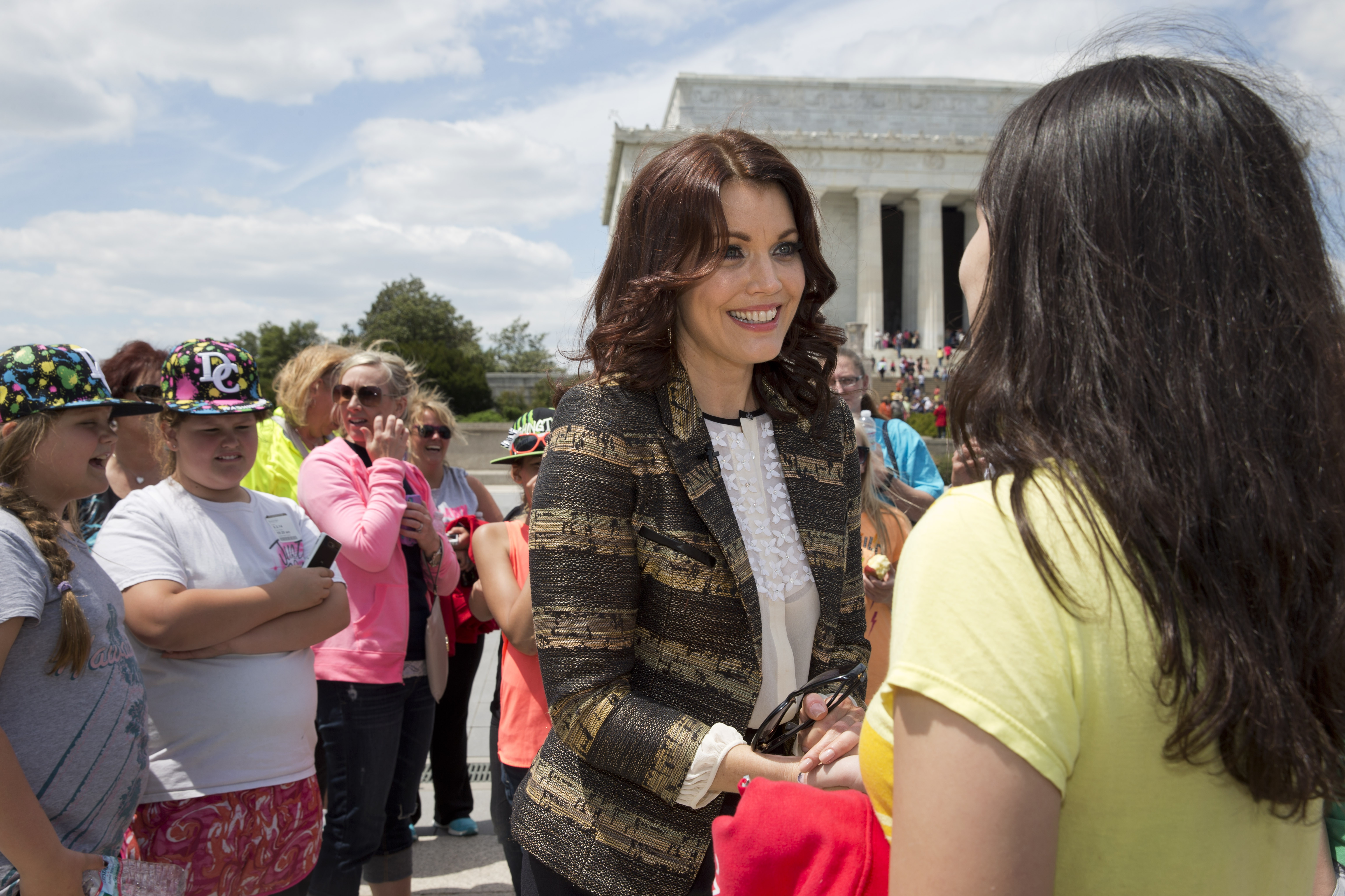 """Bellamy Young, who plays first lady Mellie Grant in the TV show """"Scandal,"""" greets a tourist on the National Mall."""