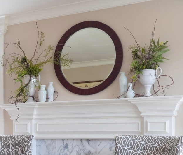 Give your fireplace mantel a spring makeover. A mirror centers this arrangement featuring a collection of white vases.