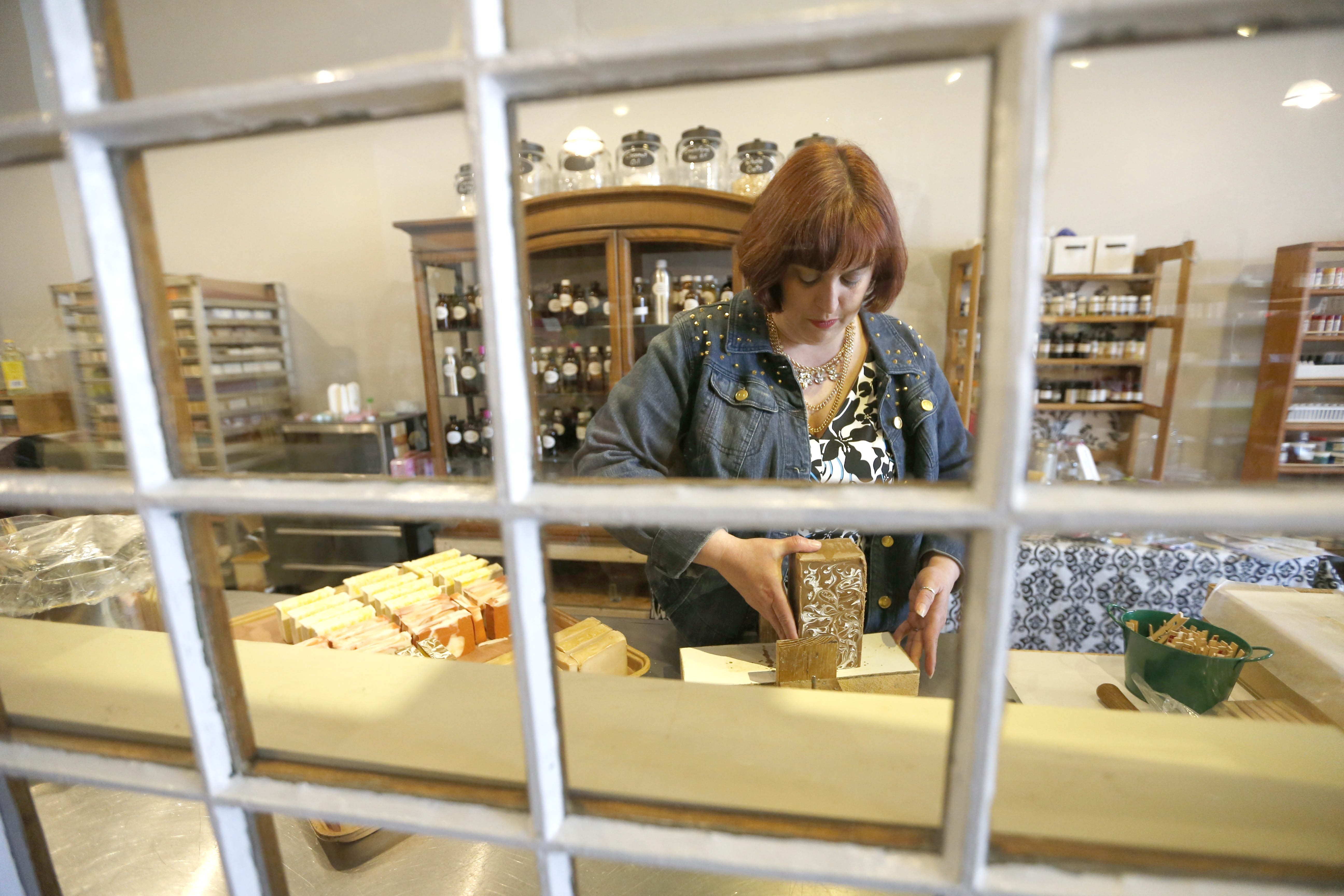 Heather Kalisiak, owner of Martinsville Soapworks, works in her in-store lab cutting handmade soap on Webster Street in NorthTonawanda.
