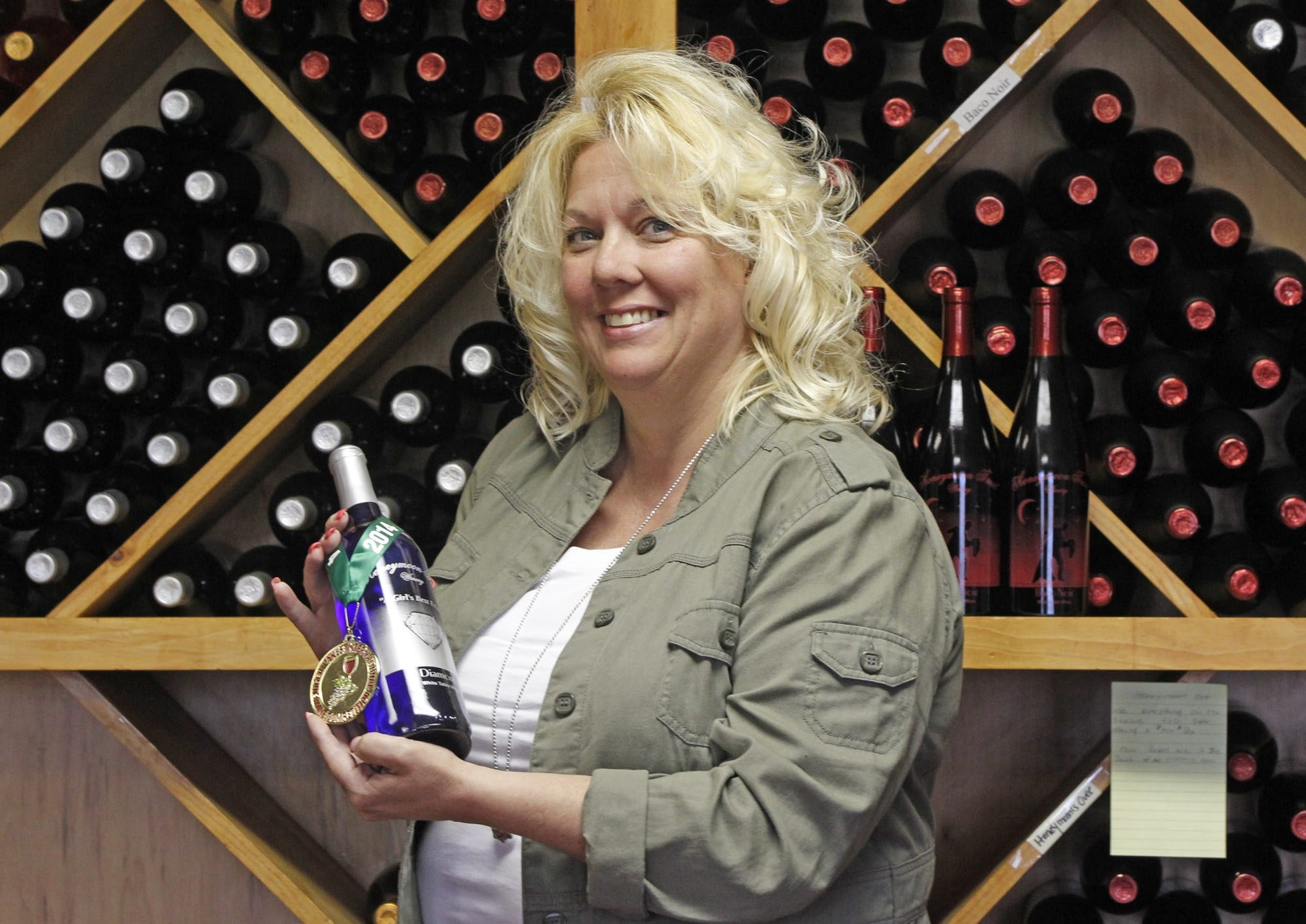 Lori Hoover, owner of Honeymoon Trail Winery in Lockport, displays one of her prize-winning wines.