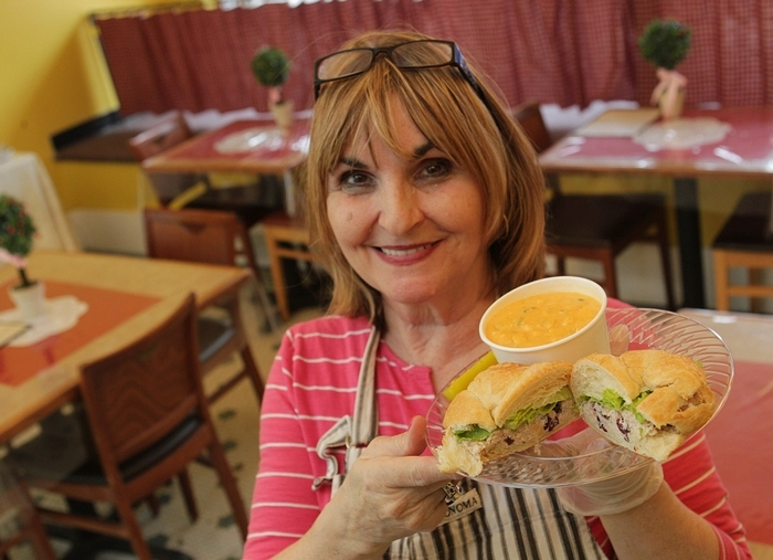 """Owner Sherri """"Mimi"""" Silora presents the chicken salad sandwich on a croissant with the Buffalo chicken wing soup at Mimi's Central Perk Cafe in Lancaster. (Sharon Cantillon/Buffalo News)"""