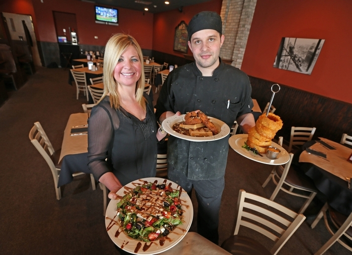Owner Lisa Galus holds a salad and the chicken and waffles entree and Chef Auston Mavrak has a tower of onion rings at Exit 2 Bar and Grille. (Robert Kirkham/Buffalo News)