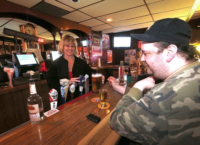 Bartender Josette Doyle delivers a mini-pitcher of beer to Mike Wilson at the Nite Cap, a casual neighborhood bar with cheap prices. (Photos by Robert Kirkham/Buffalo News)