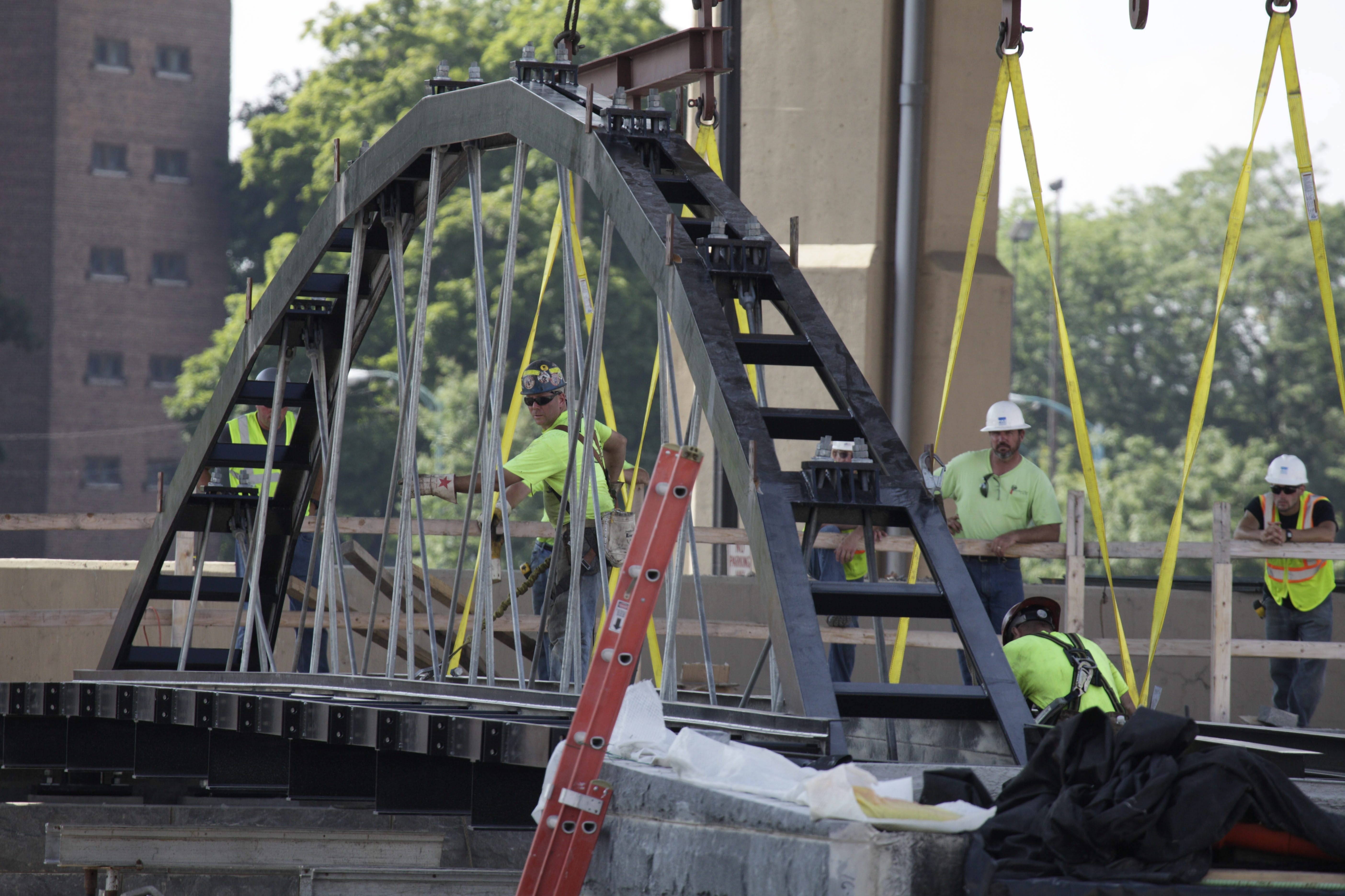 Workers position a Whipple truss bridge Monday over the historically aligned canal at Canalside. The bridge is similar to the one at the nearby Commercial Slip.