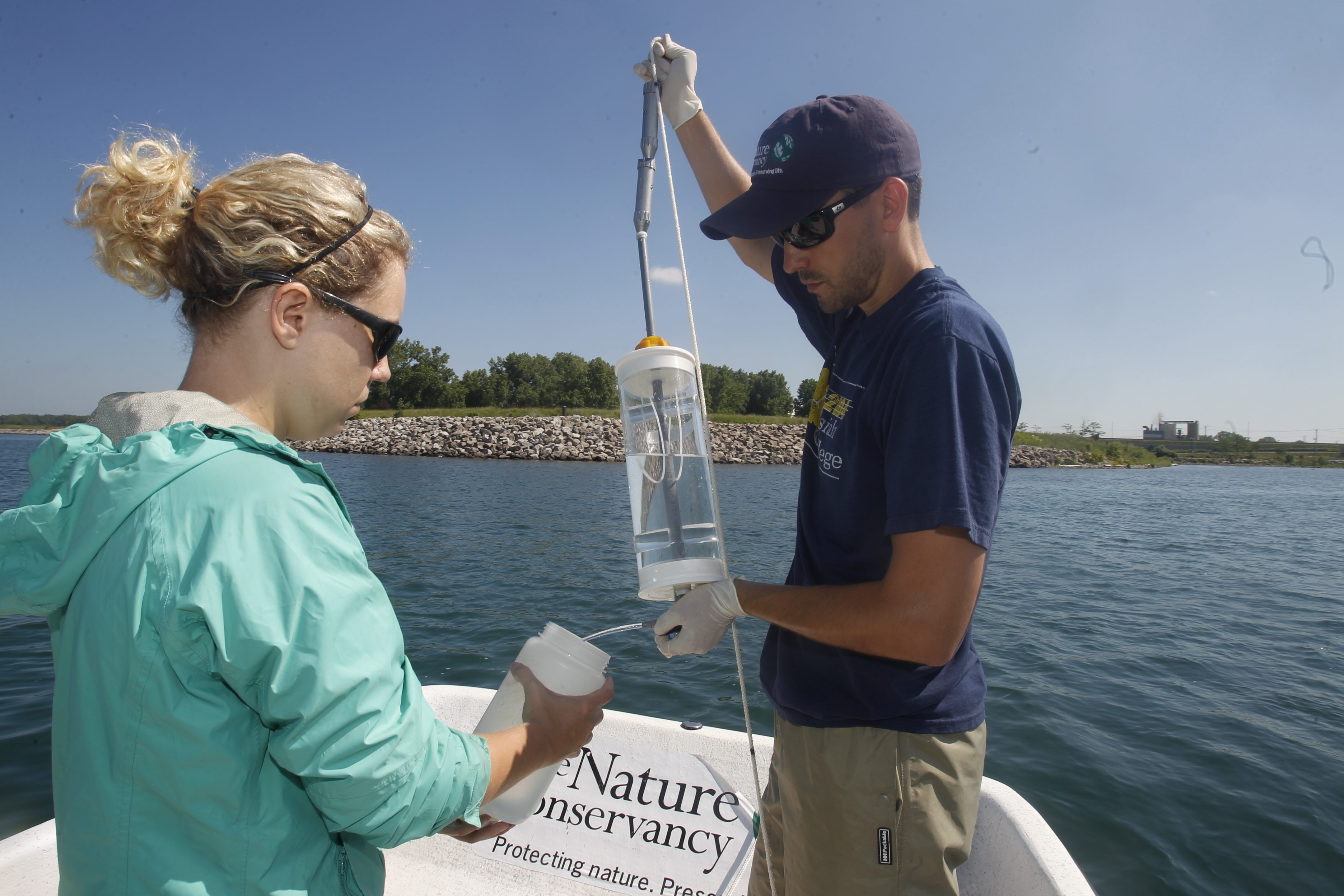 Andrew Tucker, right, an Aquatic Ecologist from the Nature Conservancy's Great Lakes Invasive Species Project, takes water samples with the help of Avril Harder. Up to 50 samples were taken from several parts of the inner harbor Friday.     Left, Travis Schepker, a biology intern, holds an Asian carp pulled from the Illinois River near Havana, Ill.