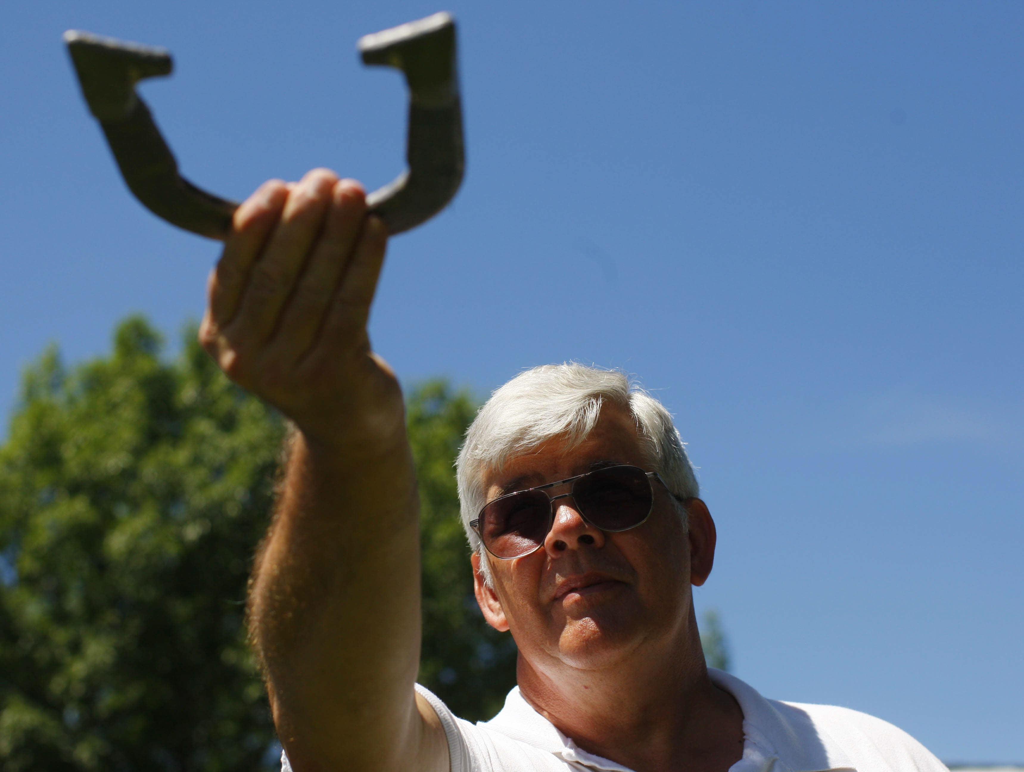 Competitive horseshoe pitcher Frank Kwiatkowski, who played a role in organizing the 2014 World Horseshoe Pitching Championship coming to the Fairgrounds next month, practices his game in the backyard of his Lakeview home.