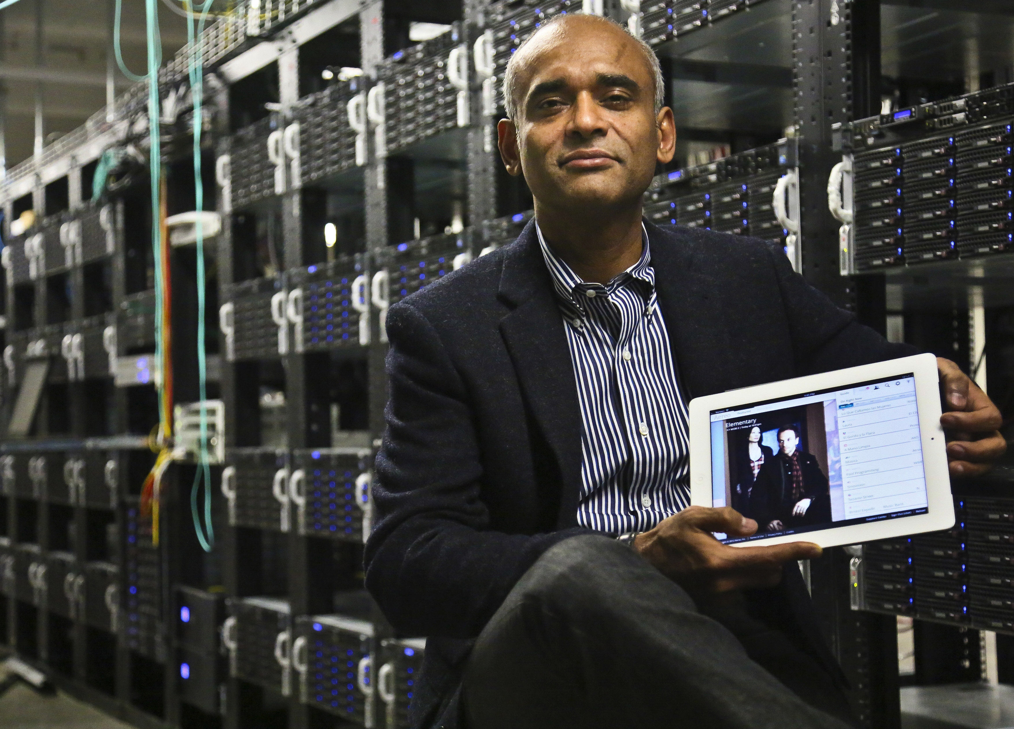 Chet Kanojia, founder and CEO of Aereo, holds a tablet displaying his company's technology.