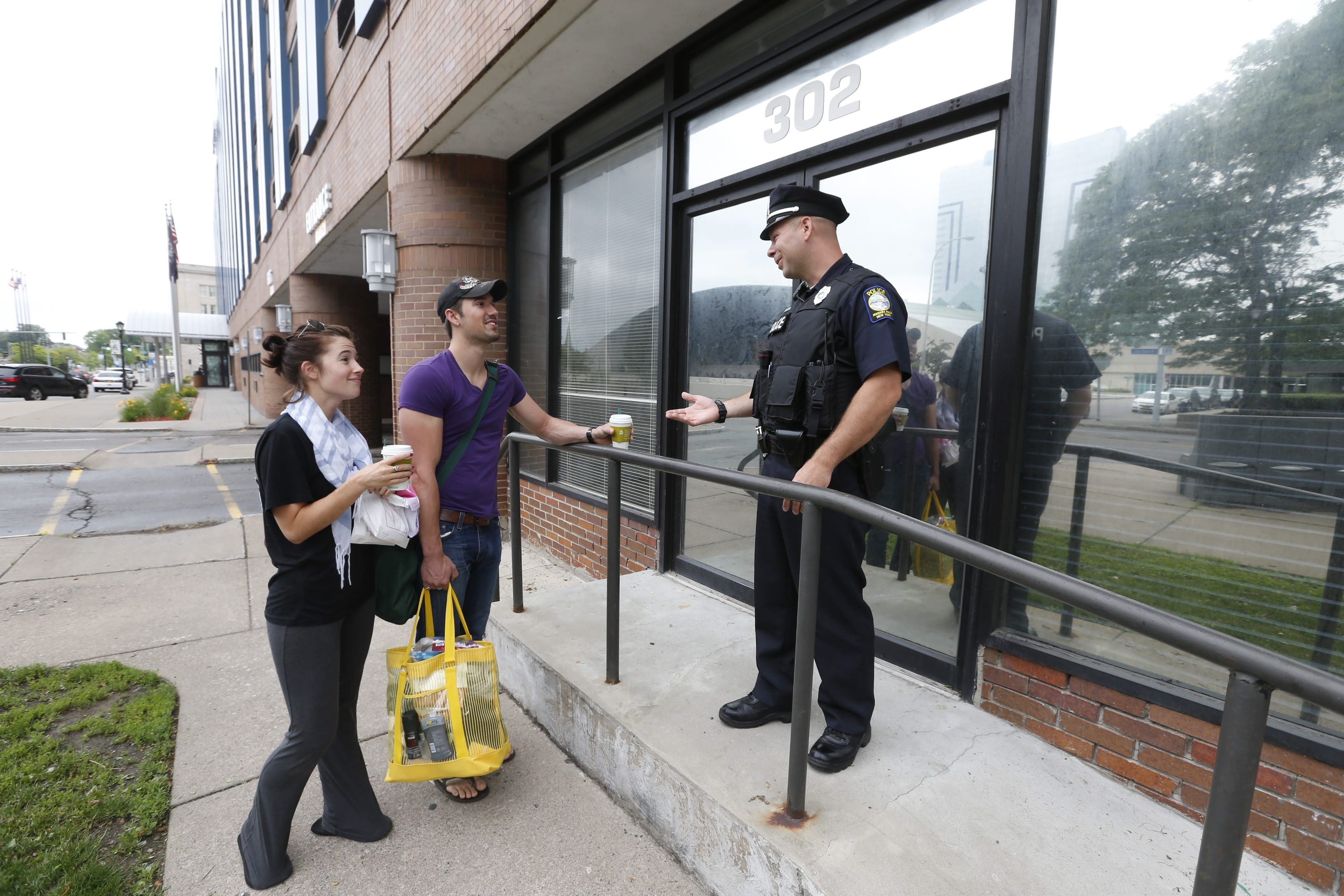 Niagara Falls Police Officer Daniel Banas visits with tourists Casey Calcei and Frank Laury, of Akron, Ohio, outside the new Downtown Rangers station at 302 Third St.