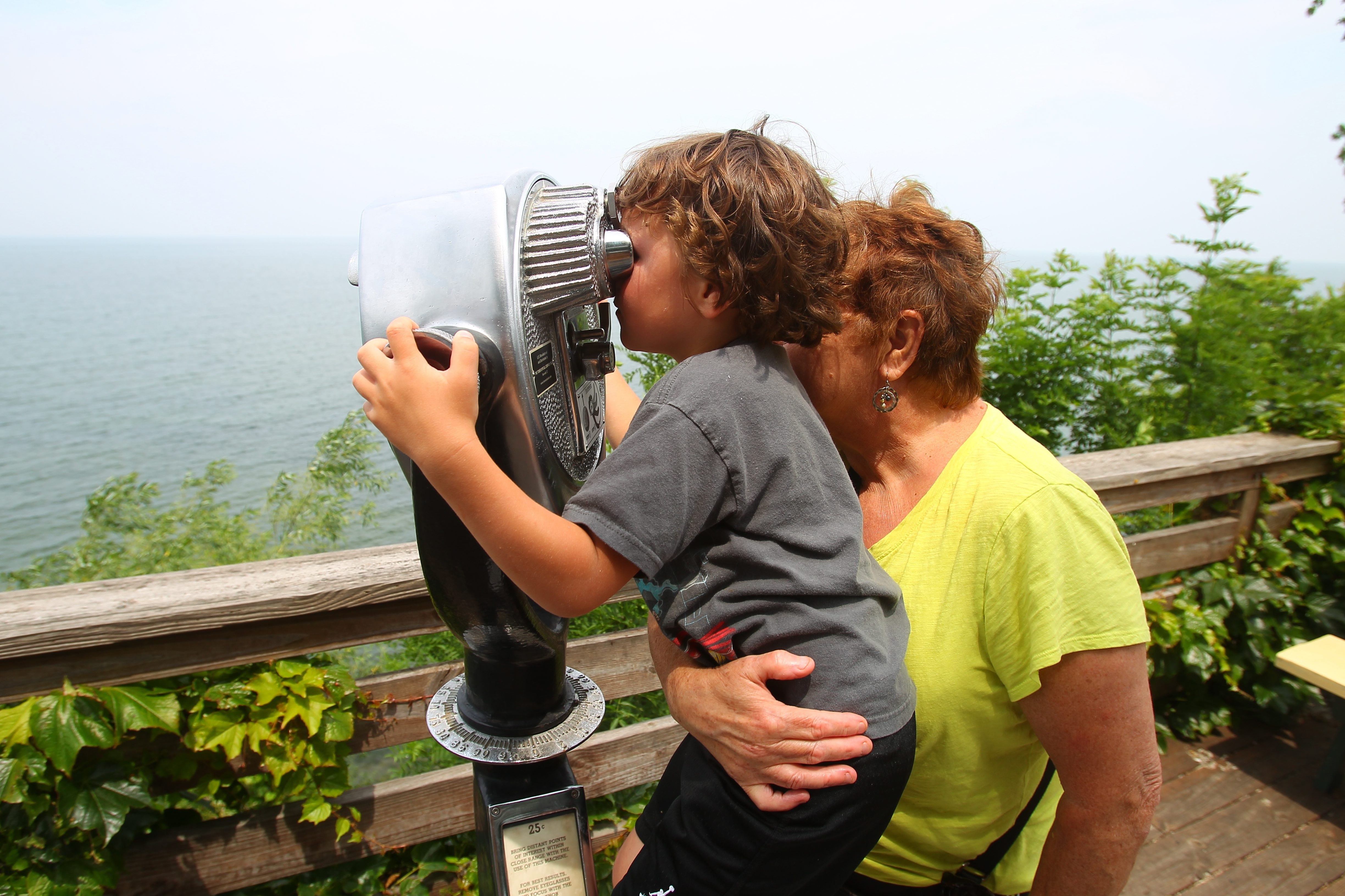Sue Hutton, of Newfane,  helps her 5 year-old grandson, Noah Orenf , as he tries to look  through a tower binocular  at Lakeview Village boardwalk  in  Olcott.
