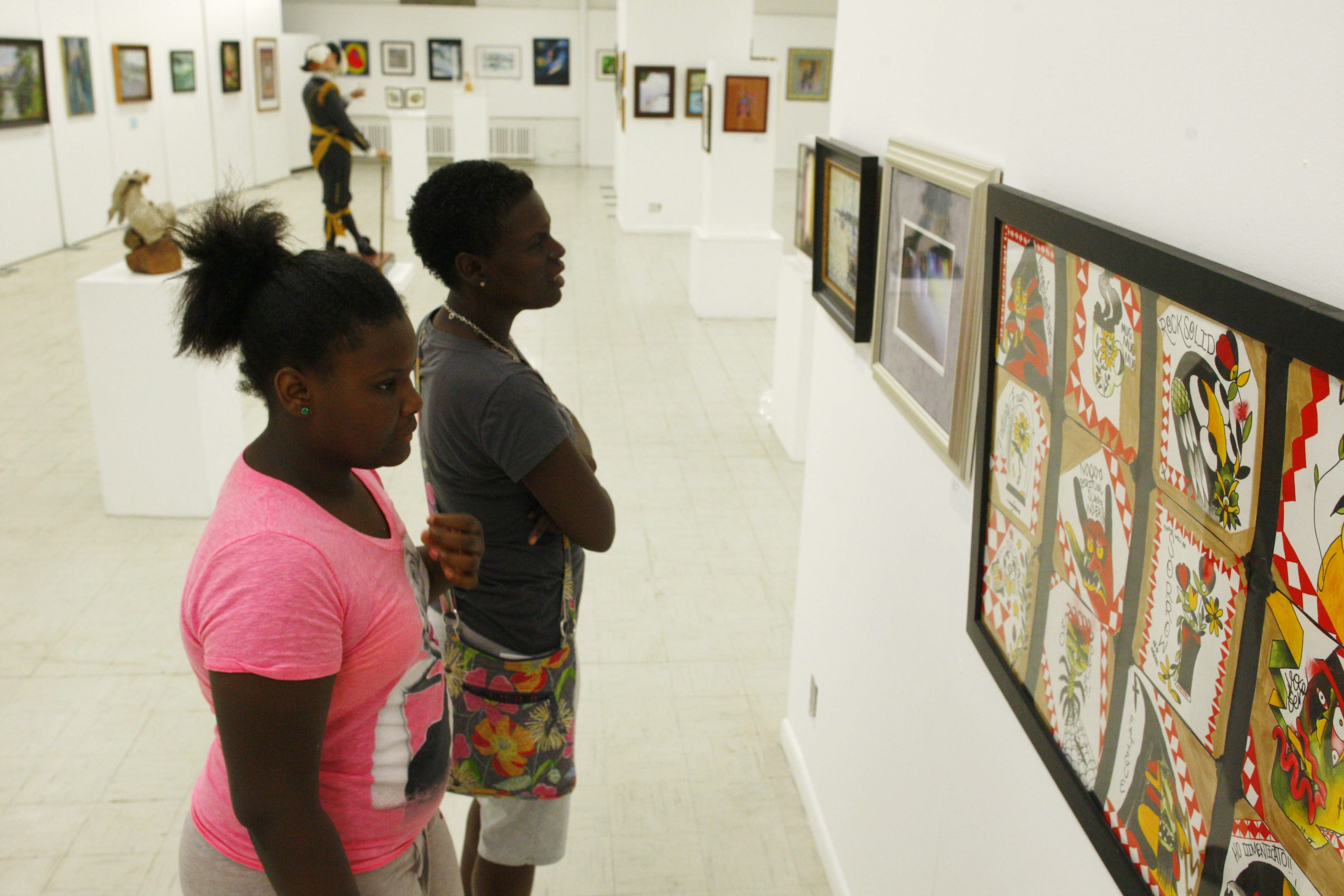 """Tiona Saunders and her daughter, Meginta Eppes, look at artwork in the annual """"Beyond the Barrel"""" show at the Niagara Arts and Cultural Center."""
