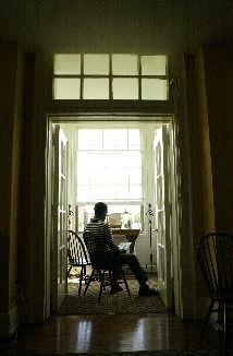 A resident of Benedict House sits in the solitude at the end of a hallway at said residence for AIDS patients.
