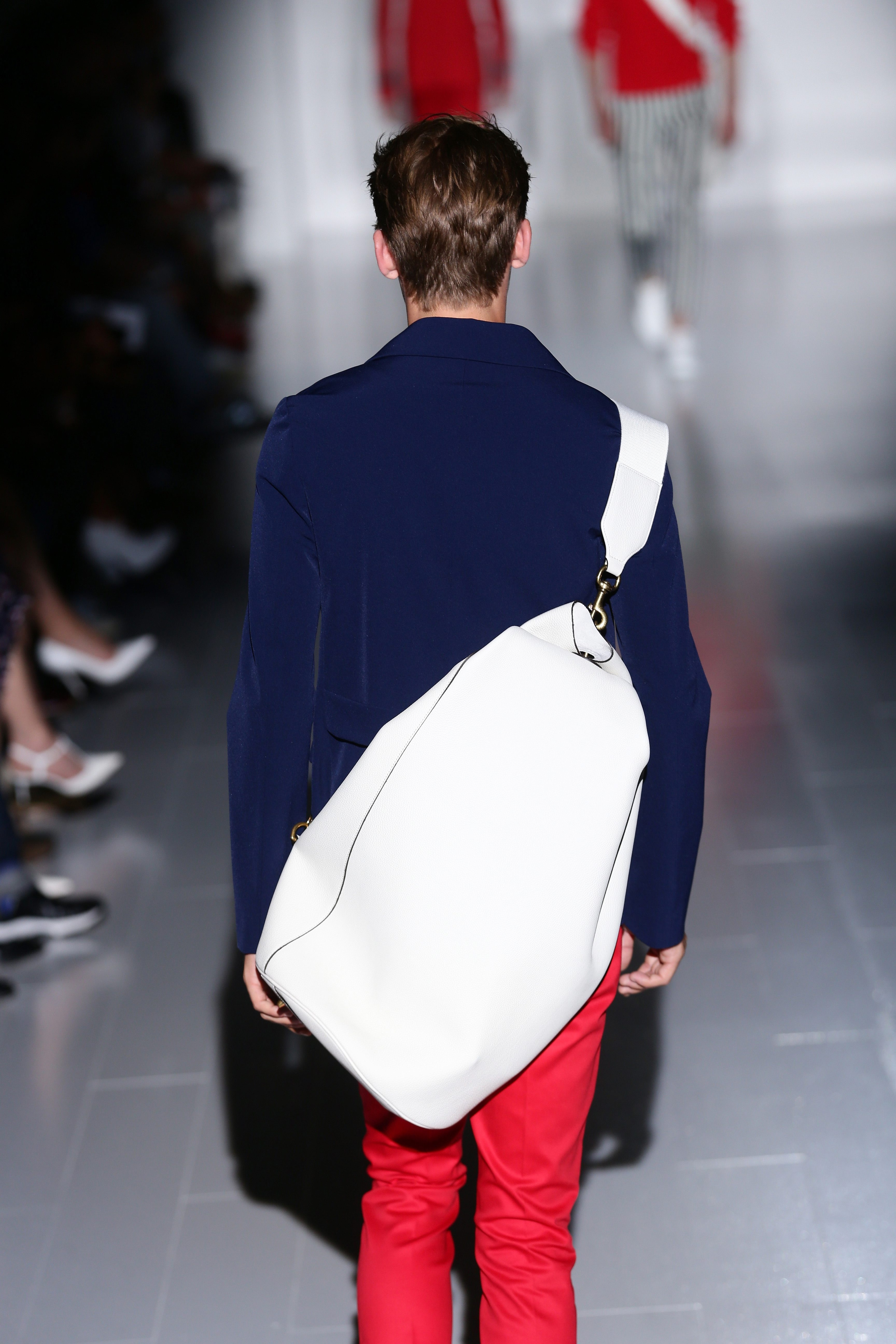 A model with white duffel bag walks the runway during last week's Gucci show in Milan.