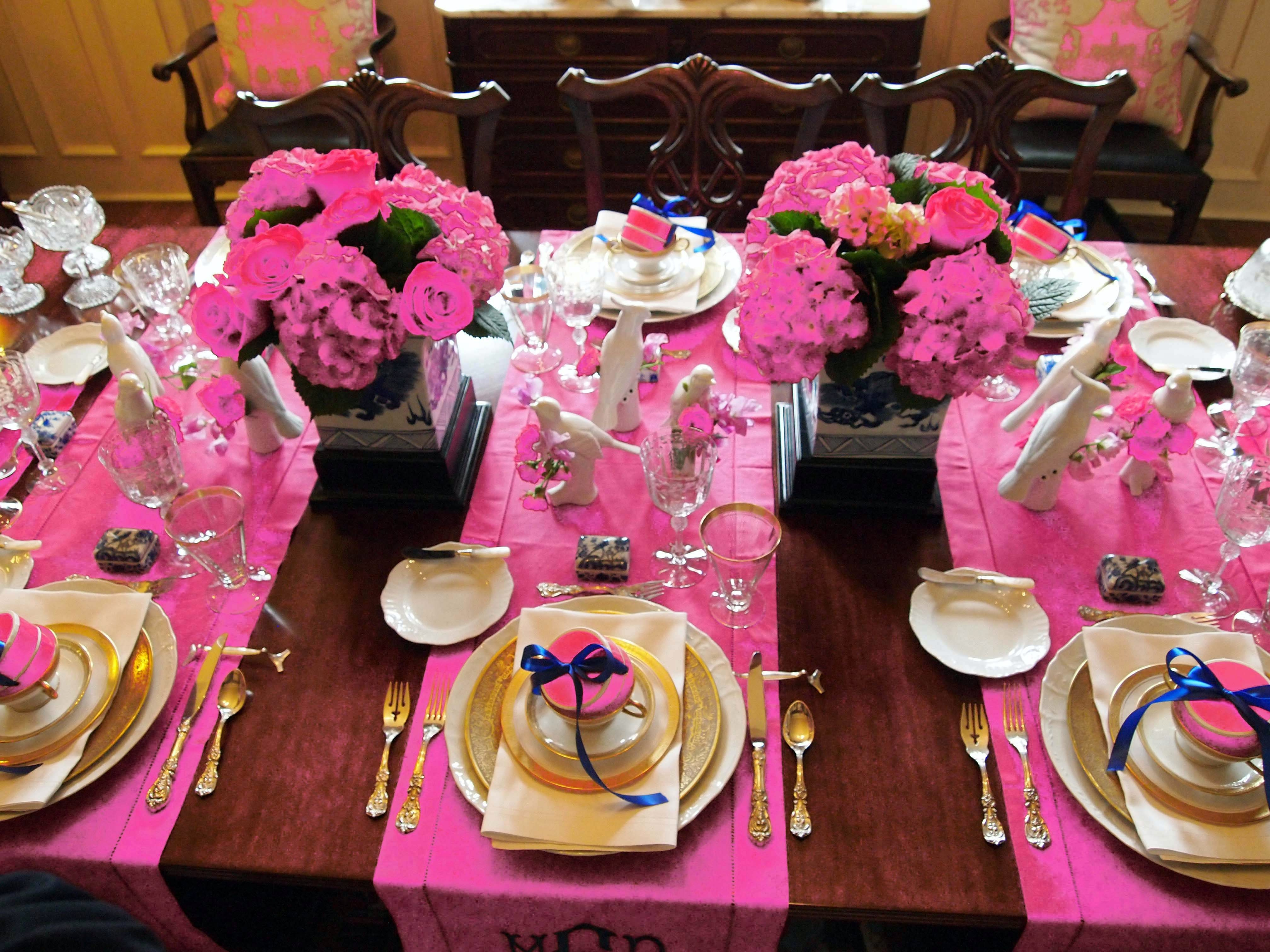 A luncheon table is dressed up with flouncy flowers, white and gold dishes and plenty of pink.