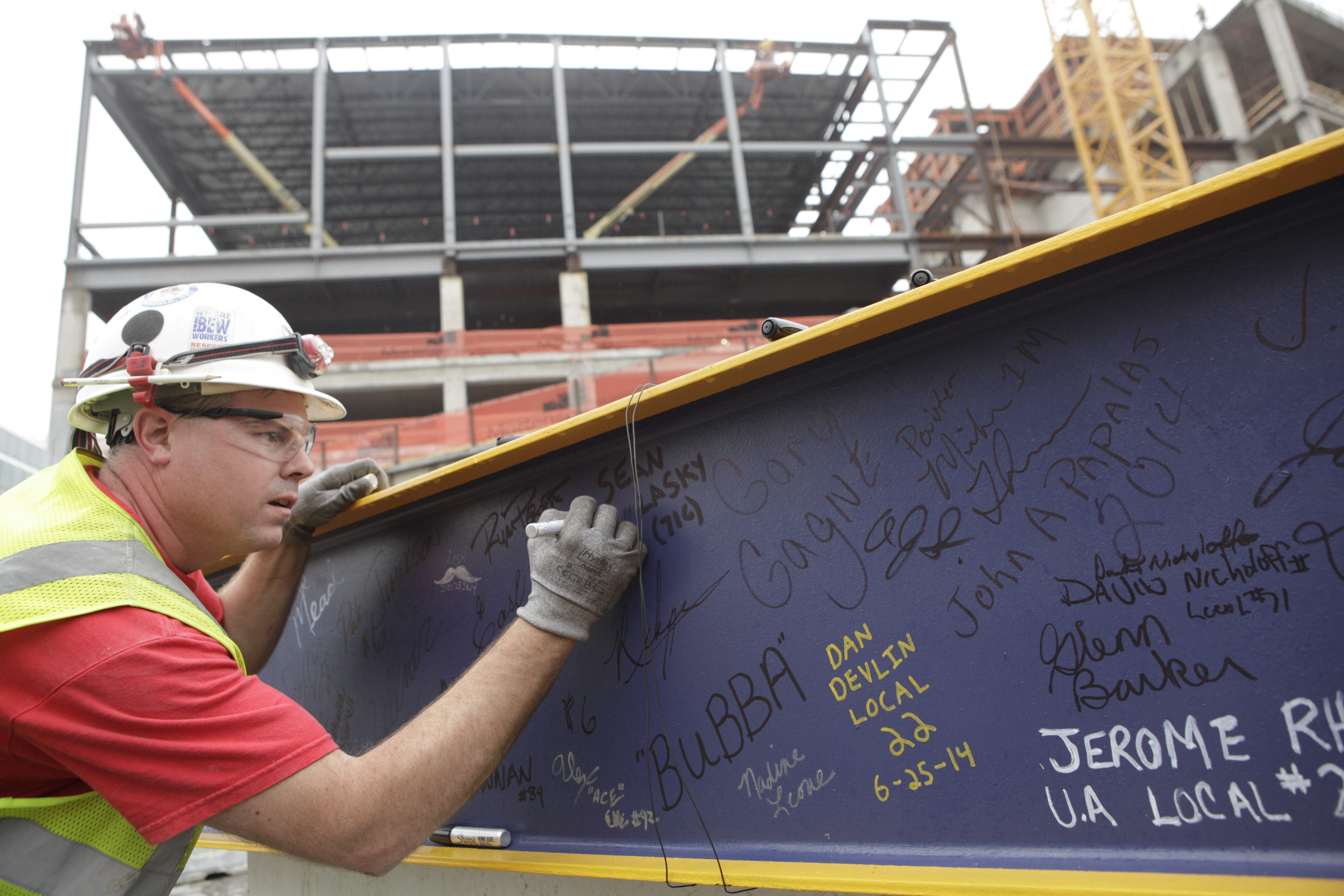 Final Beam: Electrician Darren Golas signs the final steel beam before it is lifted into place Wednesday at HarborCenter, while, clockwise, ironworkers watch as the final beam is guided into place. HarborCenter President John Koelmel, above, was on hand.
