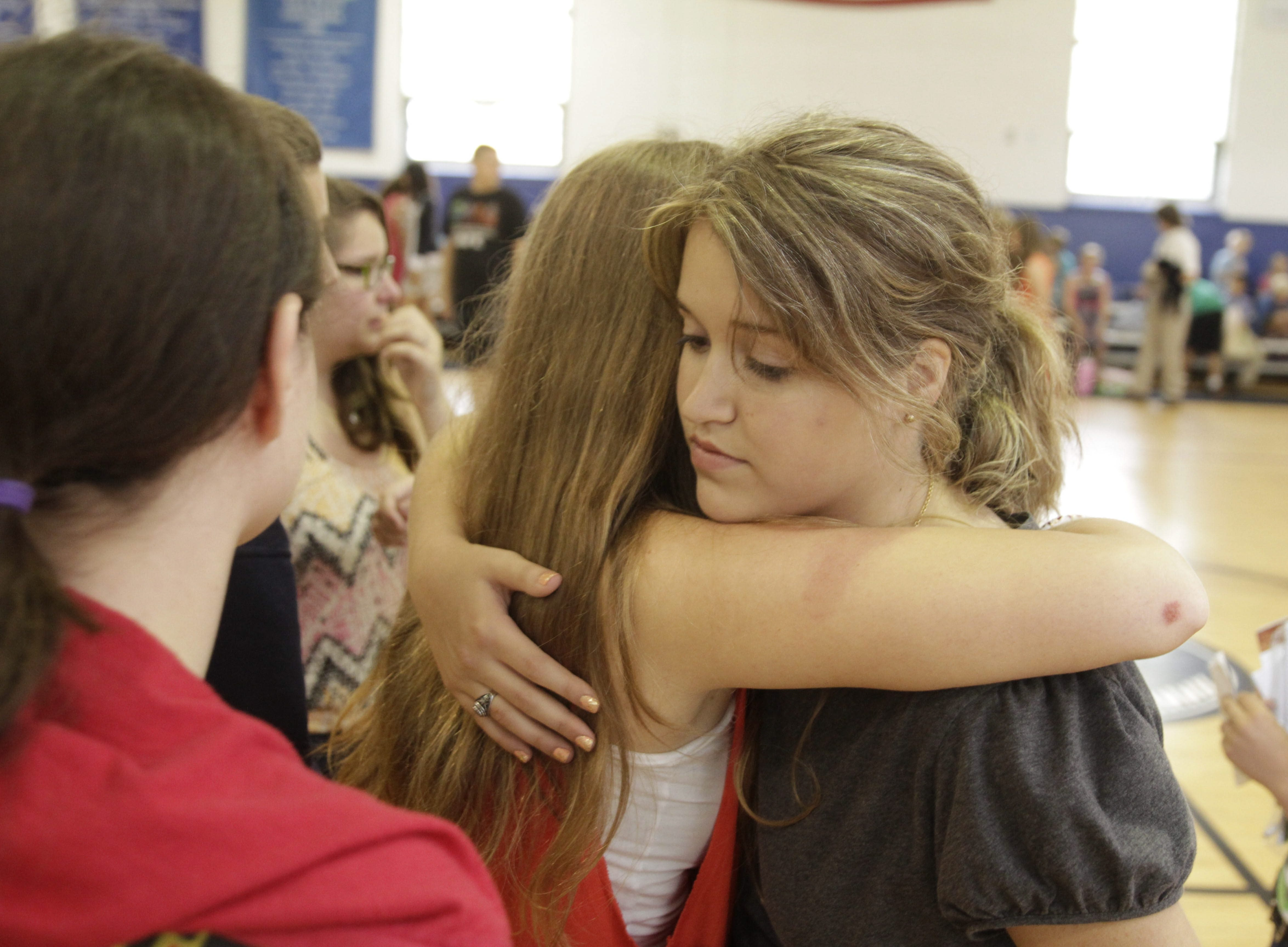 An emotional embrace is one of many at Annunciation School on Wednesday, as students, parents, faculty and staff gather to say goodbye, a scene similar to those at nine other schools being closed by the Diocese of Buffalo.