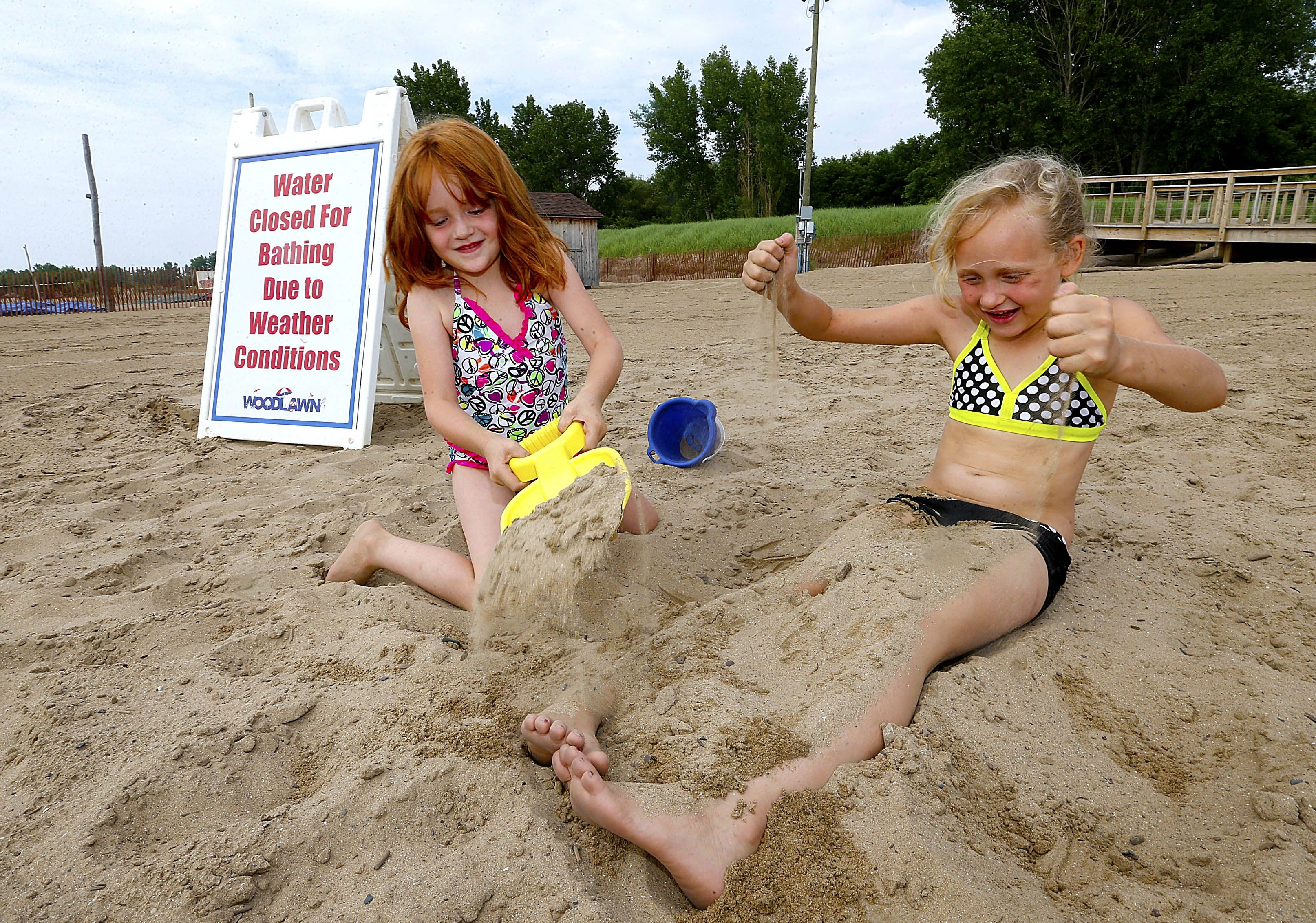 Kierstin Thompson, 5, left, covers her sister Lily Ann, 7, with sand Tuesday as they play next to a warning sign at Woodlawn Beach. The two Buffalo children made the best of things after the water was deemed off-limits.