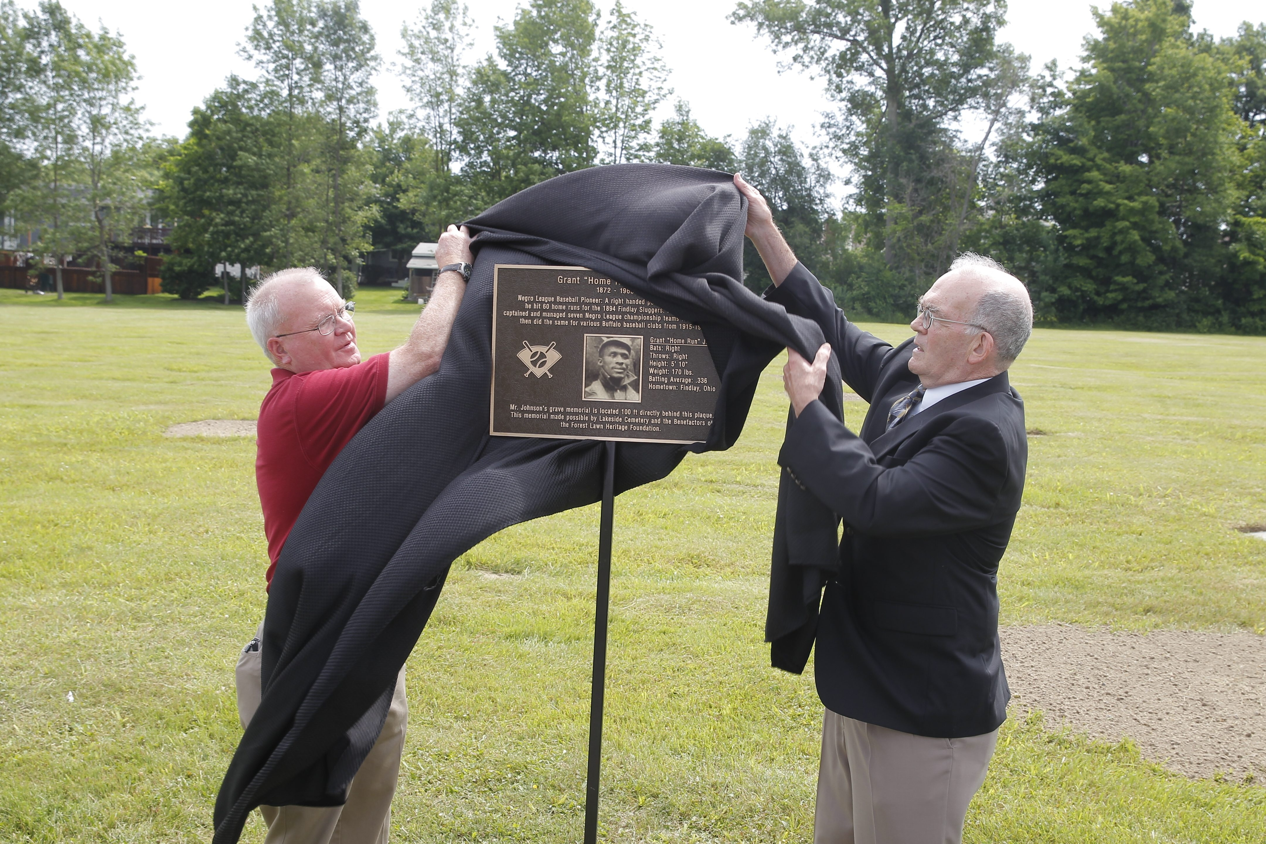 "Howard W. Henry, right, a Society for American Baseball Research member and a supporter of the Negro Leagues Baseball Grave Marker Project, unveils plaque honoring Grant ""Home Run"" Johnson at Lakeside Cemetery in Hamburg, helped by historian Patrick B. Kavanaugh."